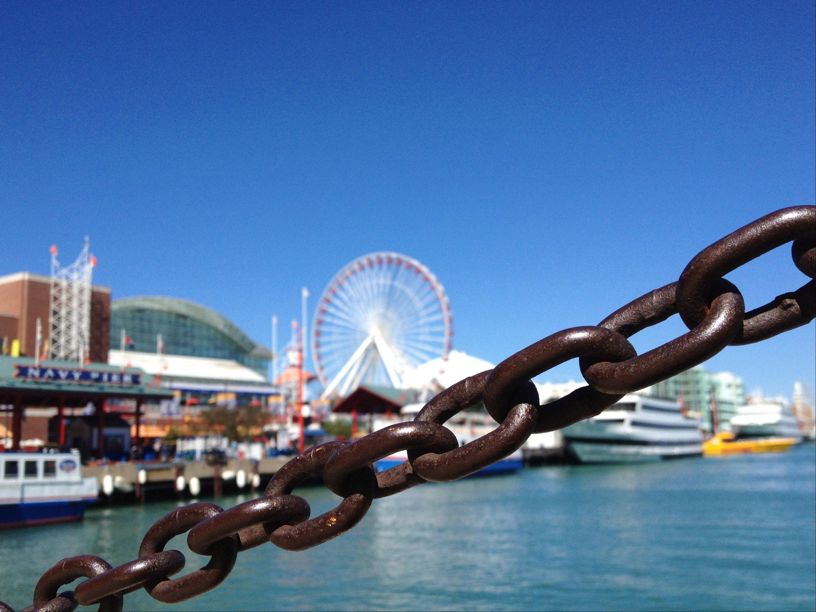 A chain stretches across the deck of Navy Pier in downtown Chicago last summer. The Ferris wheel can be seen in the background along Lake Michigan.