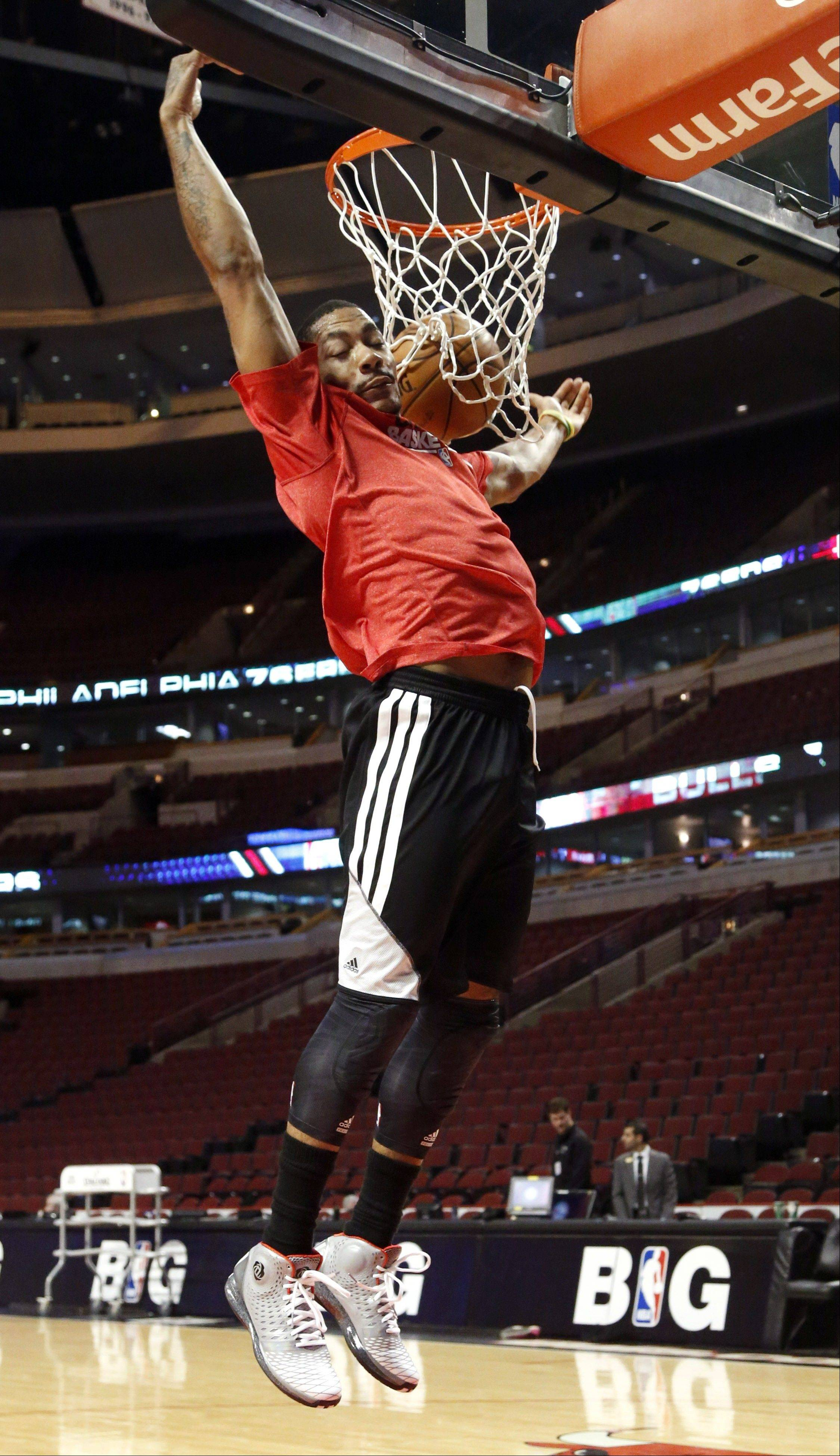 Bulls guard Derrick Rose dunks during a workout before an NBA basketball game against the Philadelphia 76ers, Thursday, Feb. 28, 2013, in Chicago. Rose remains out while recovering from a knee injury.