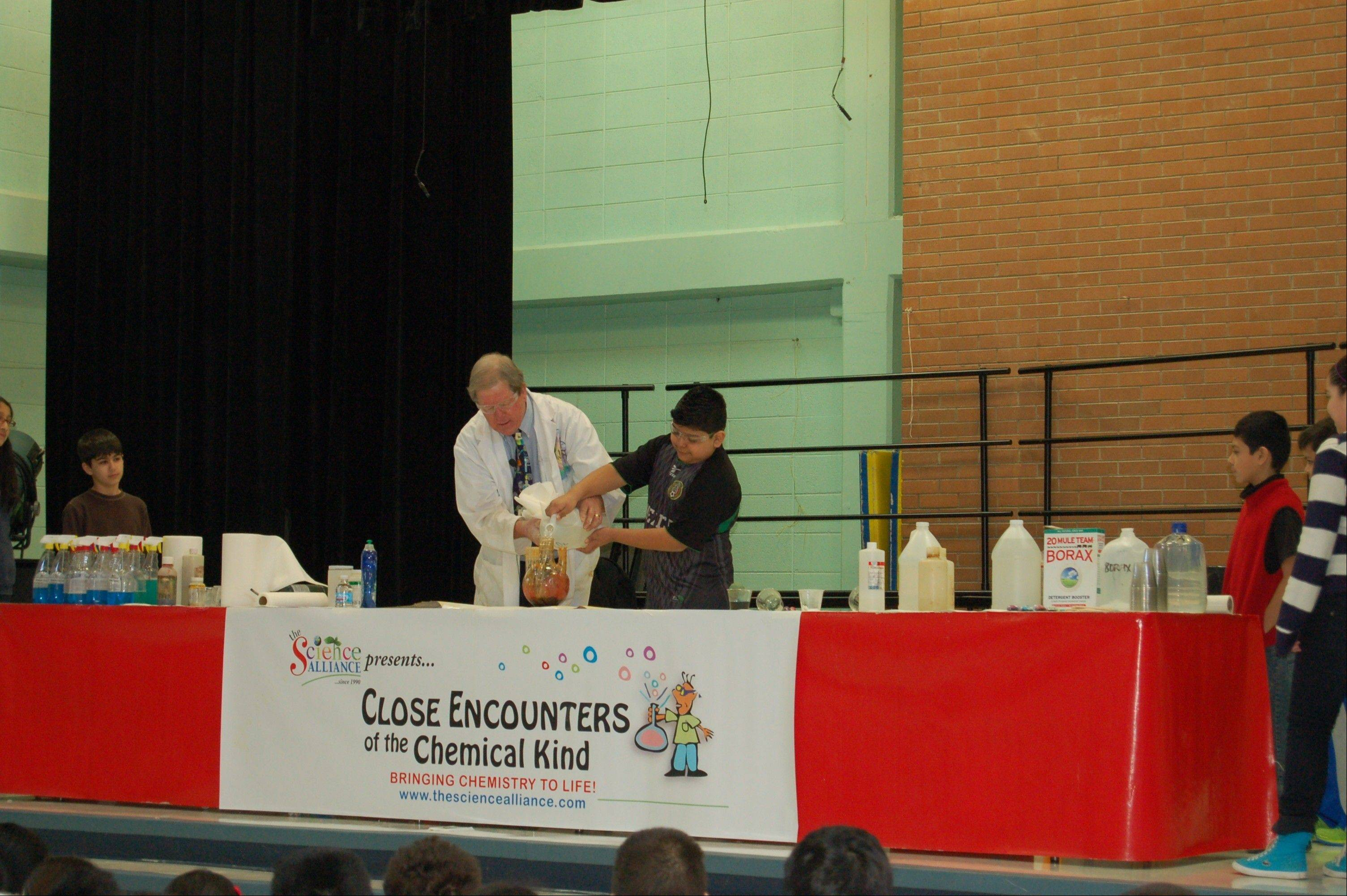 "Forest fifth-grader, Israel Zacarias, joins Science Alliance creator Bill Bosworth in demonstrating chemical reactions and experiments during the ""Close Encounters of the Chemical Kind"" assembly."