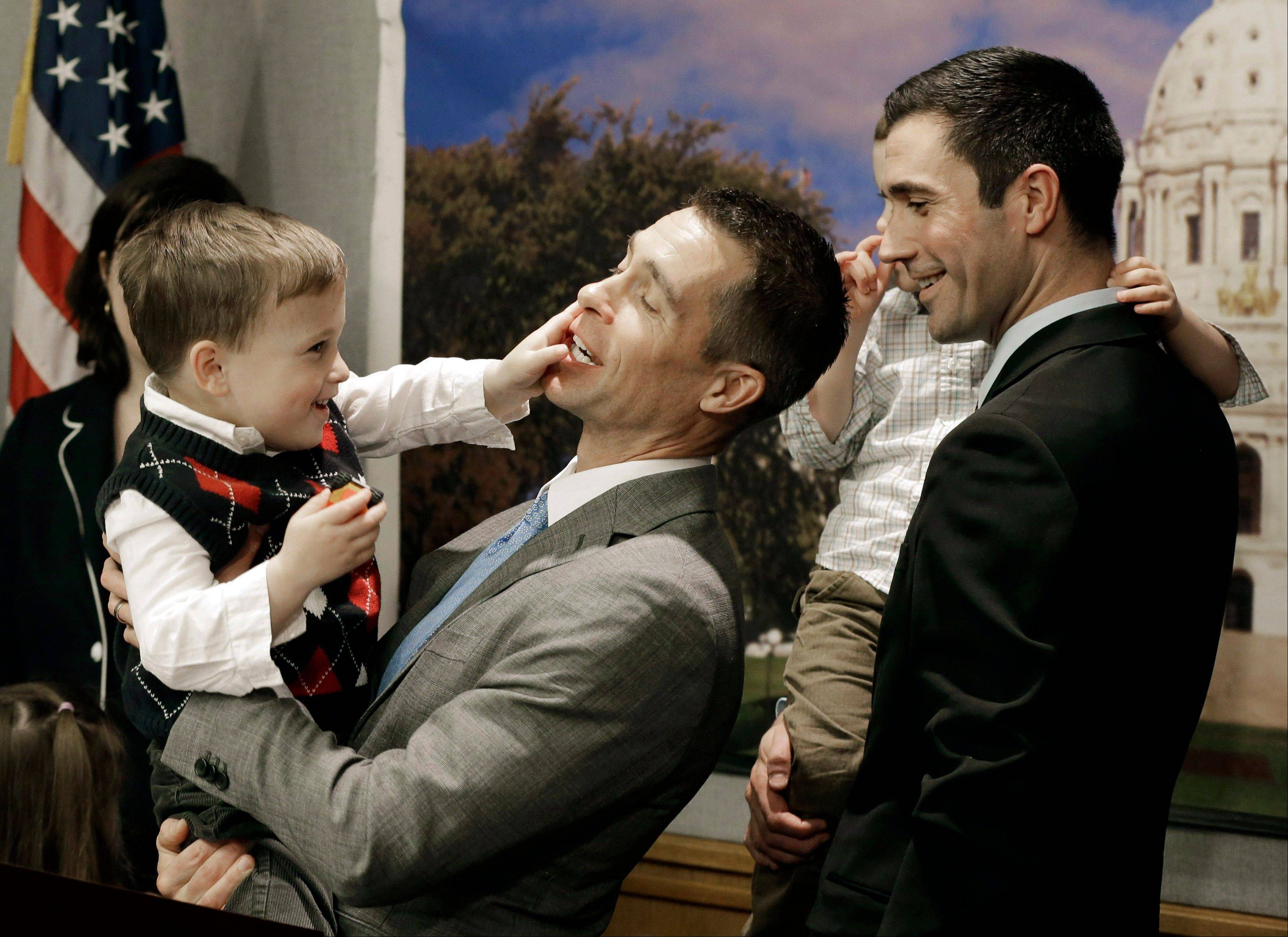 Dr. Paul Melchert, left, gets interrupted Wednesday by his son, Emmett, as he attempts to address the media while his partner James Zimerman, right, holds Emmett�s twin brother, Gabriel, during a news conference in St. Paul, Minn. Lawmakers introduced a bill Wednesday to legalize gay marriage in Minnesota.