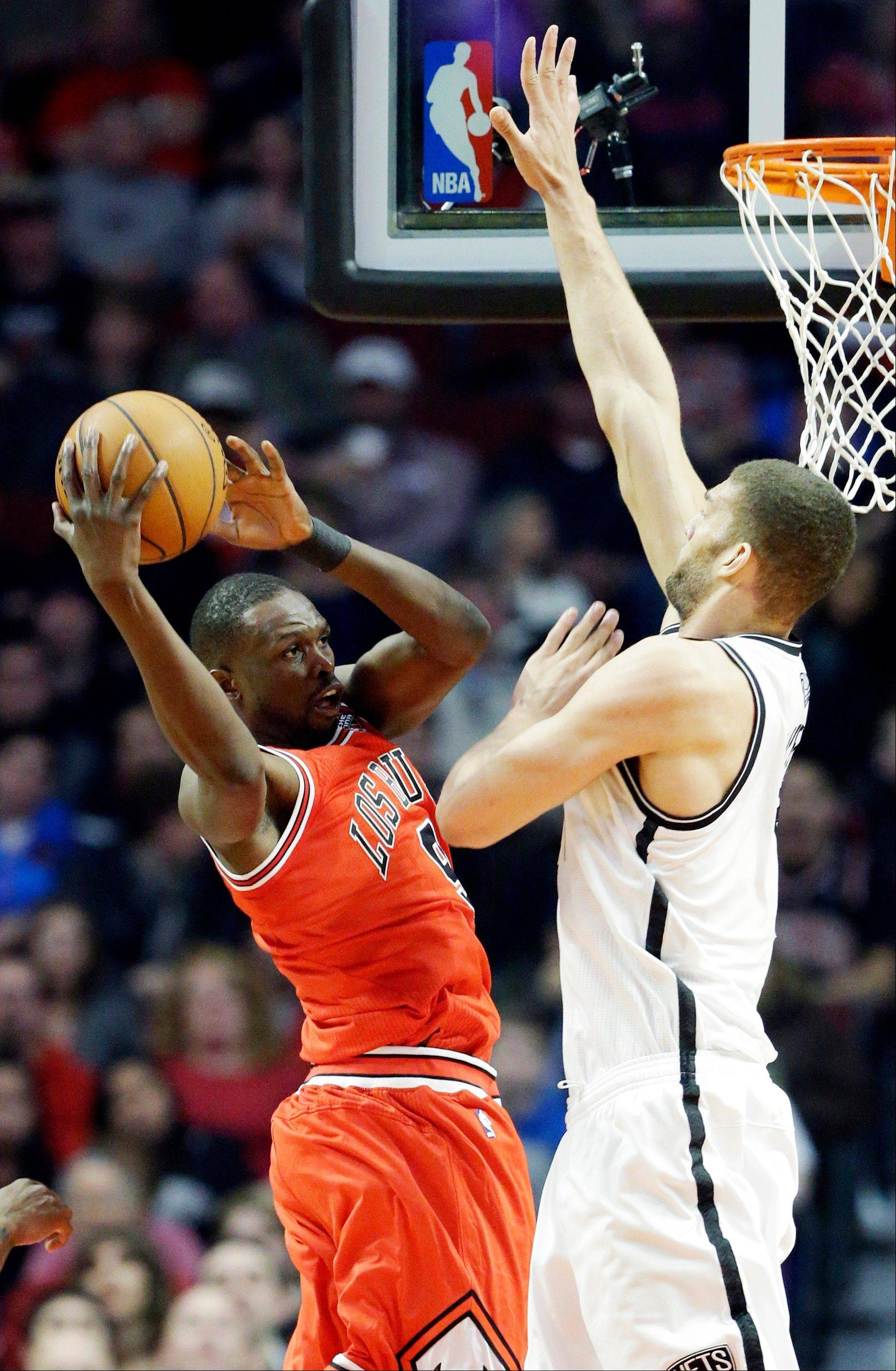 Chicago Bulls forward Luol Deng, left, of South Sudan, looks to a pass against Brooklyn Nets center Brook Lopez during the first half of an NBA basketball game in Chicago on Saturday, March 2, 2013. (AP Photo/Nam Y. Huh)