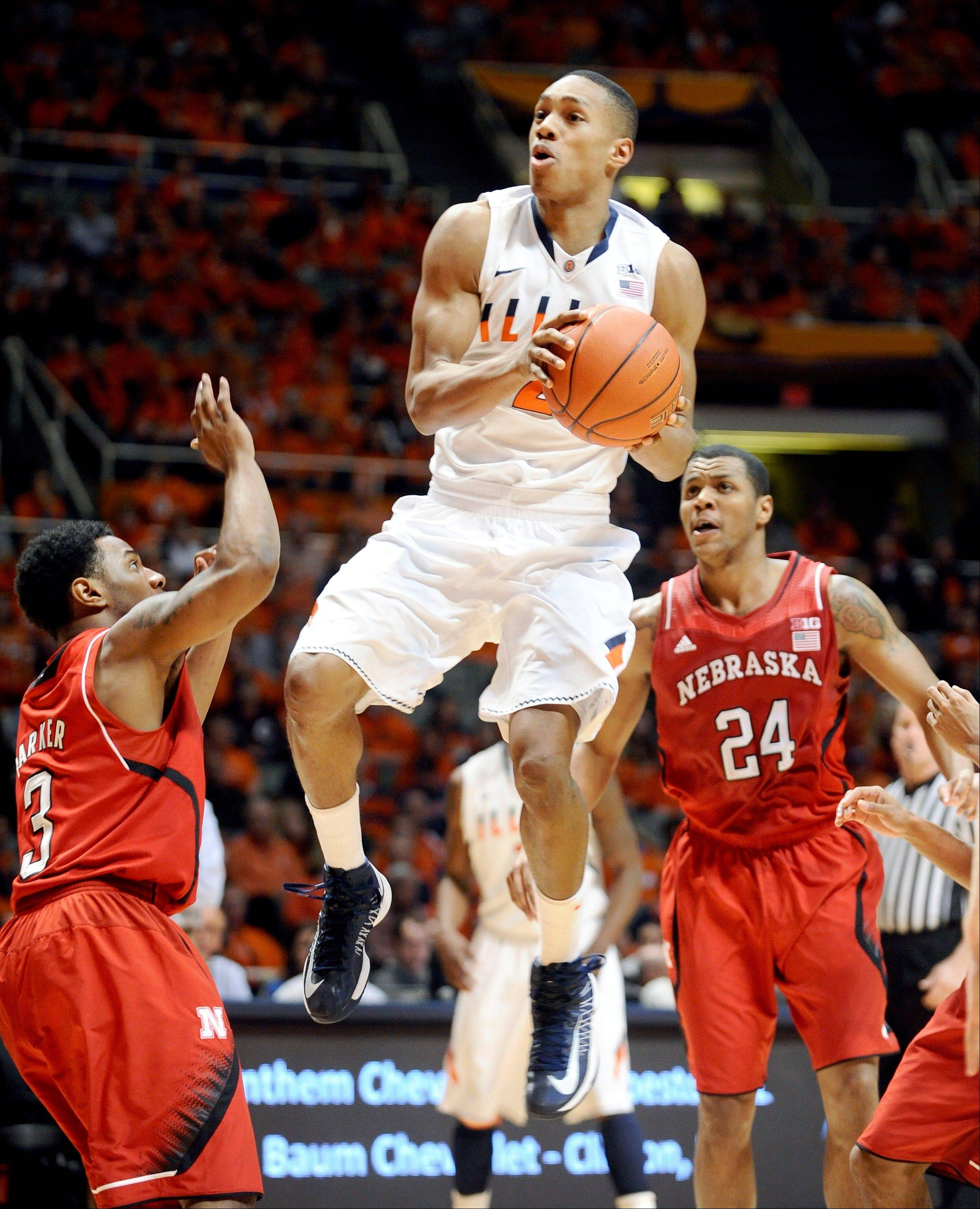 Illinois' Joseph Bertrand (2) tries to go up for a basket against Nebraska's Benny Parker (3) and Dylan Talley (24) during the first half of an NCAA college basketball game in Champaign, Ill., on Saturday, March 2, 2013. (AP Photo/Heather Coit)