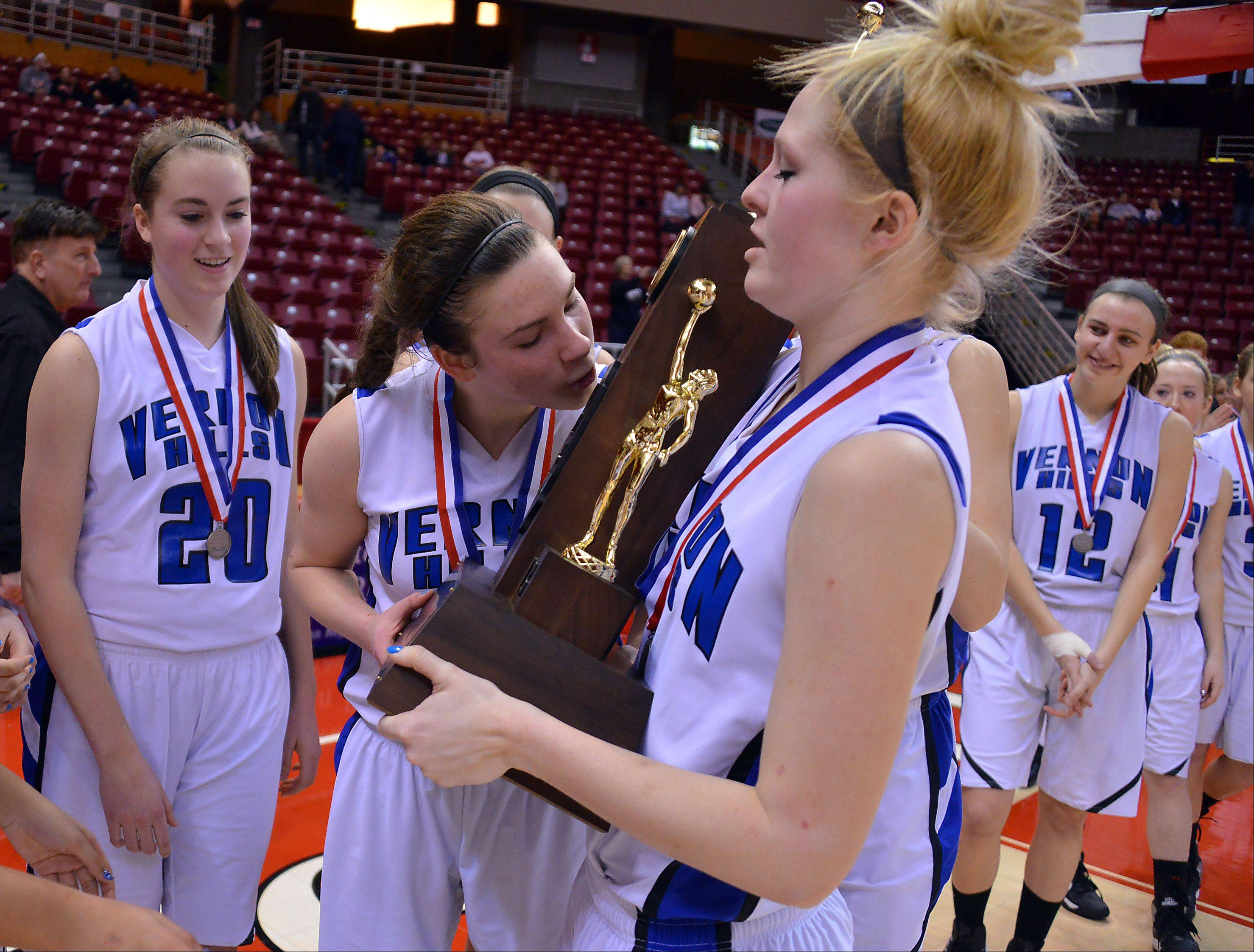 Vernon Hills' Brie Bahlmann kisses the second place trophy as teammate Sydney Smith holds it after they lost to Quincy Notre Dame Notre Dame in the Class 3A state girls basketball in Normal on Saturday.