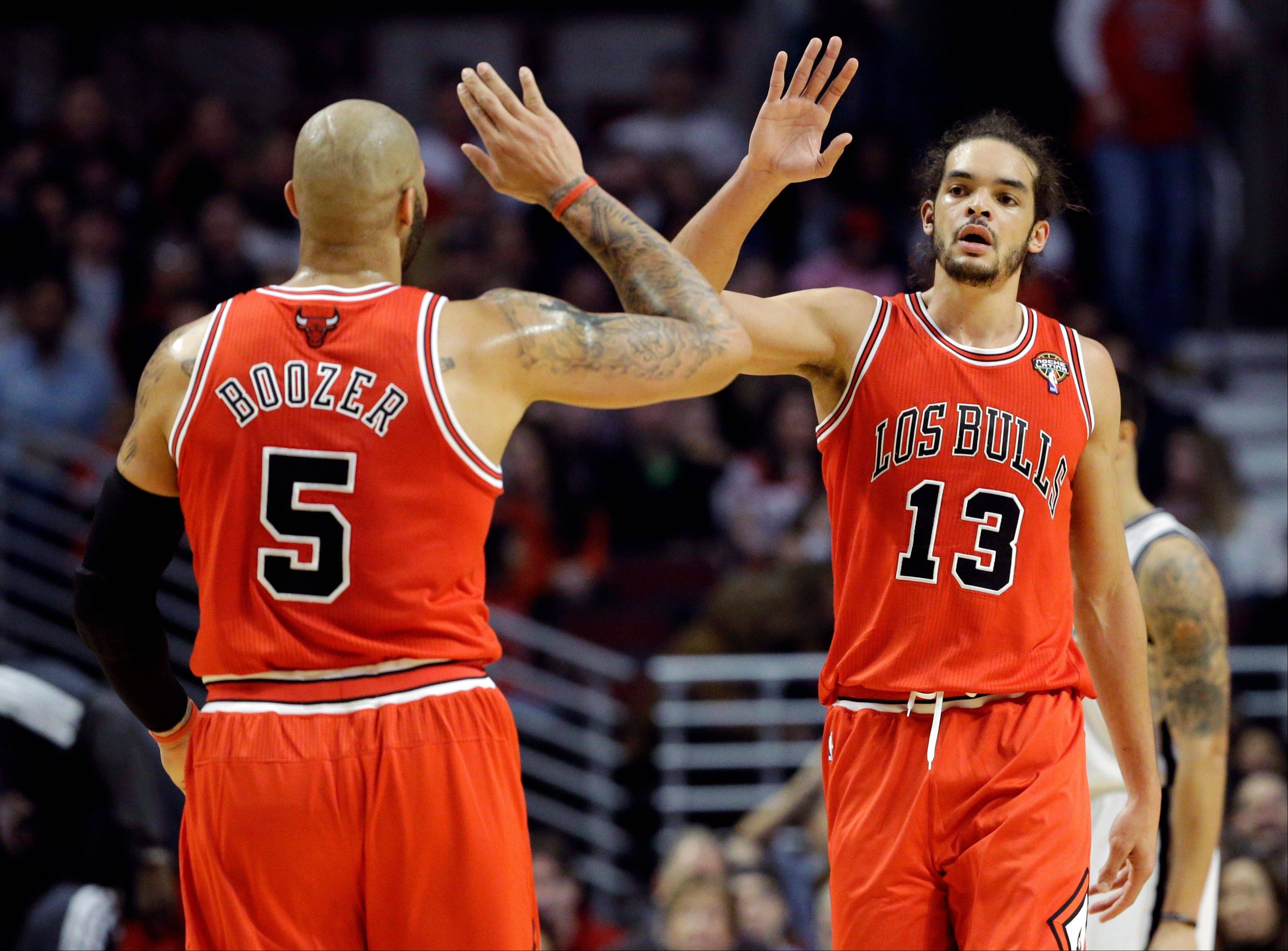 Joakim Noah, right, celebrates with forward Carlos Boozer after Brooklyn Nets forward Kris Humphries fouled during the first half of an NBA basketball game in Chicago on Saturday, March 2, 2013.