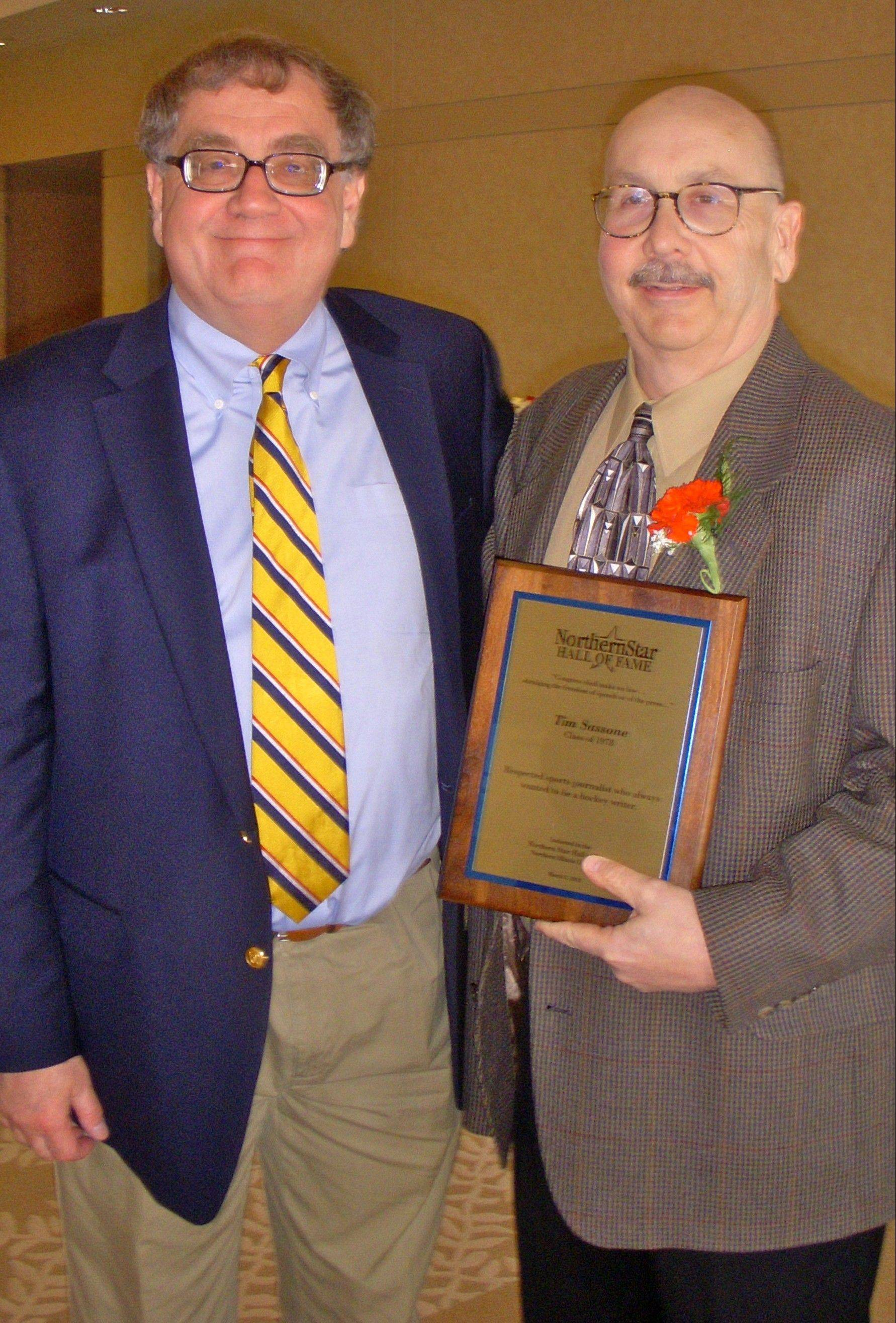 Daily Herald Sportswriter Tim Sassone receives his Northern Star Hall of Fame plaque Saturday from former NIU sports information director Michael Korcek.