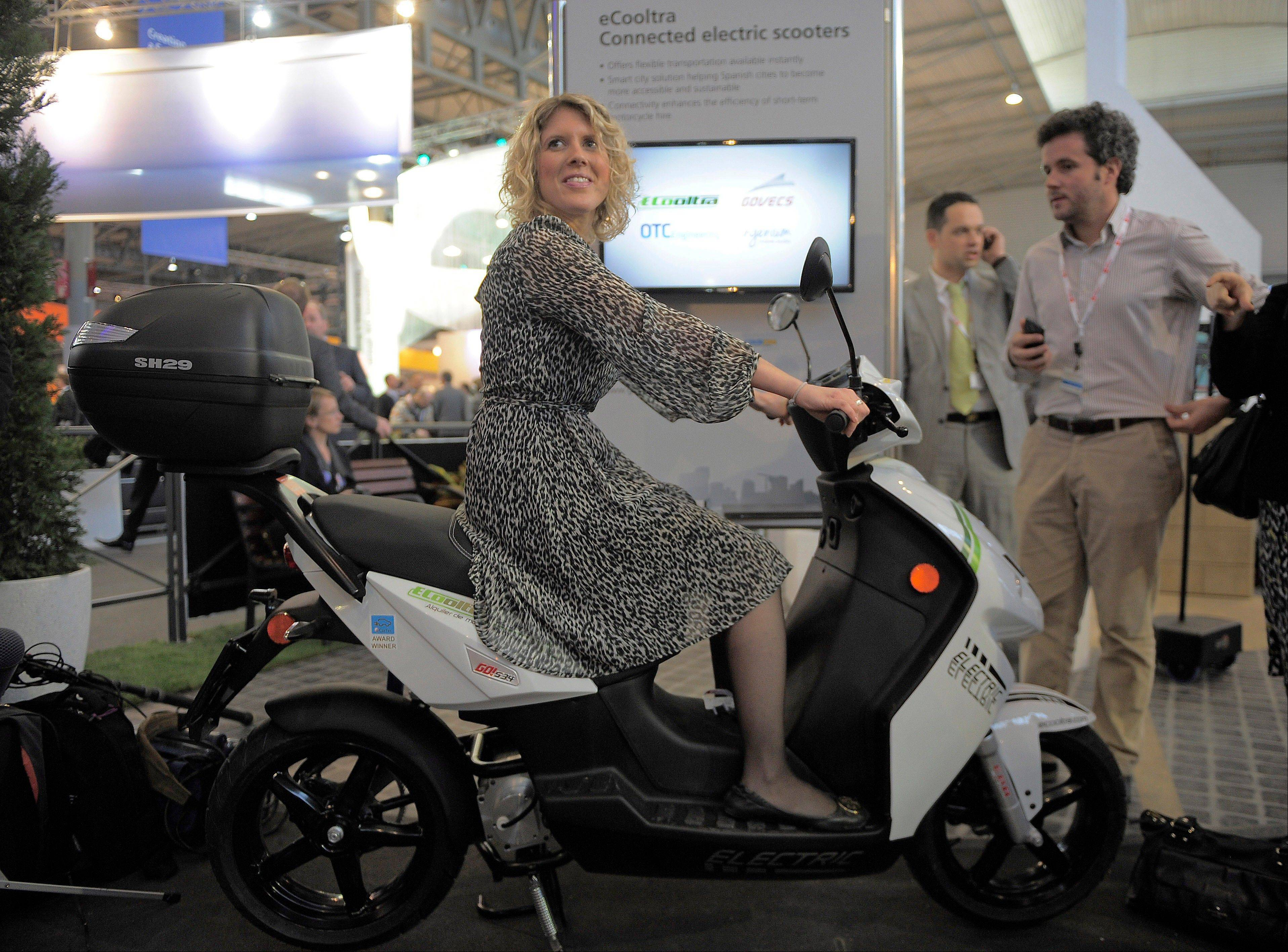 A woman sits on an eCooltra Connected electric scooters Tuesday at the Mobile World Congress, the world's largest mobile phone trade show, in Barcelona, Spain.