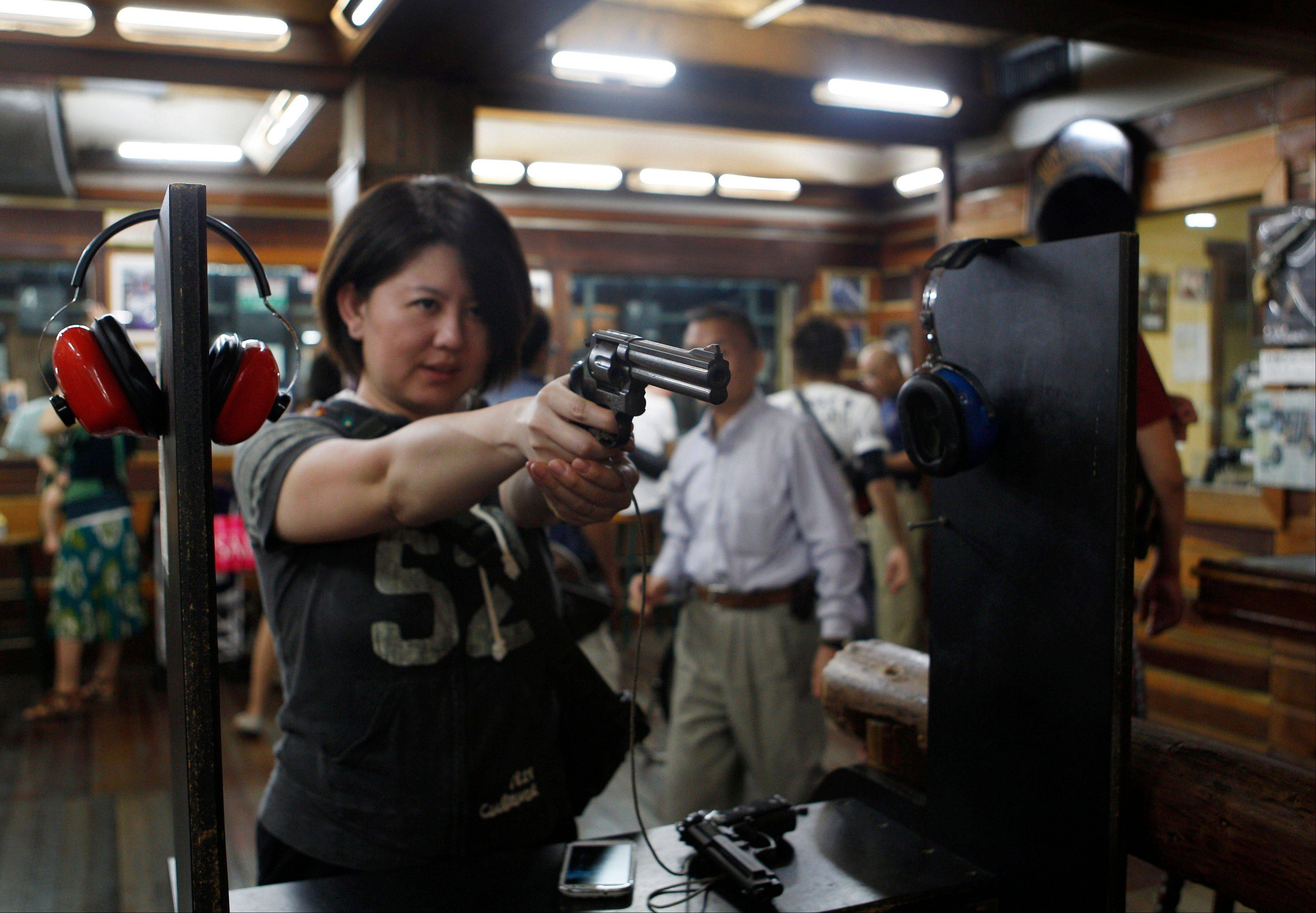Japanese tourist Natsue Matsumoto, 38, warms up for a round of shooting at the Western Frontier Village range in Tamuning, Guam. Gun tourism is a big attraction on the tiny U.S. territory, drawing thousands of visitors who can't own guns in their own countries.