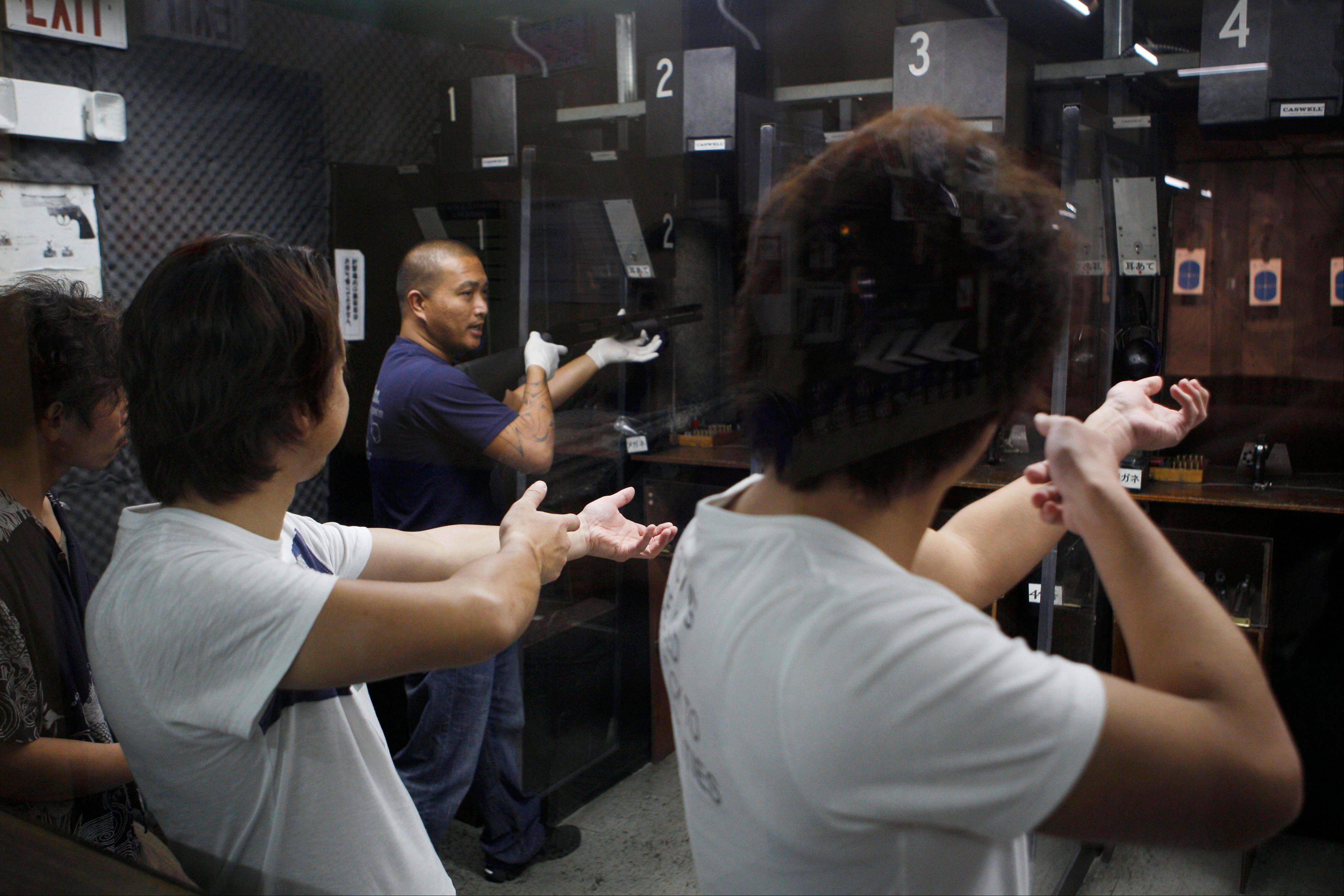 Japanese tourists are taught how to fire a rifle at the Western Frontier Village range in Tamuning, Guam.