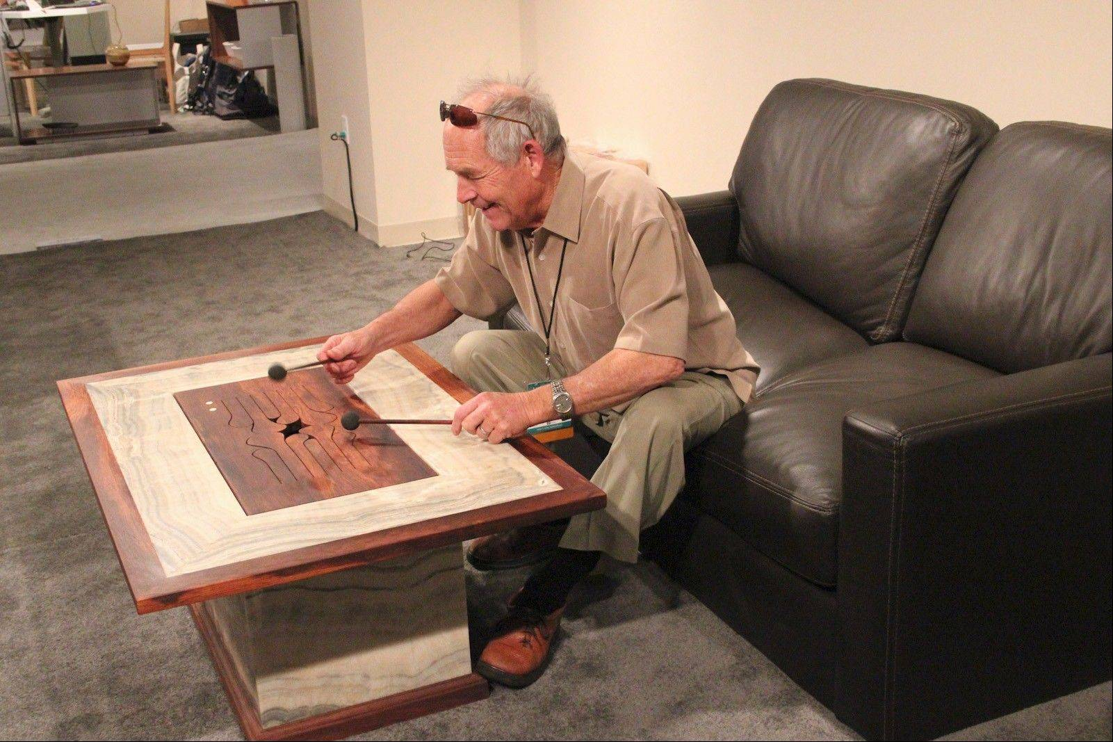 Michael Thiele of the Hardwood Music company plays this acoustic coffee table constructed of Guatemalan rose wood.