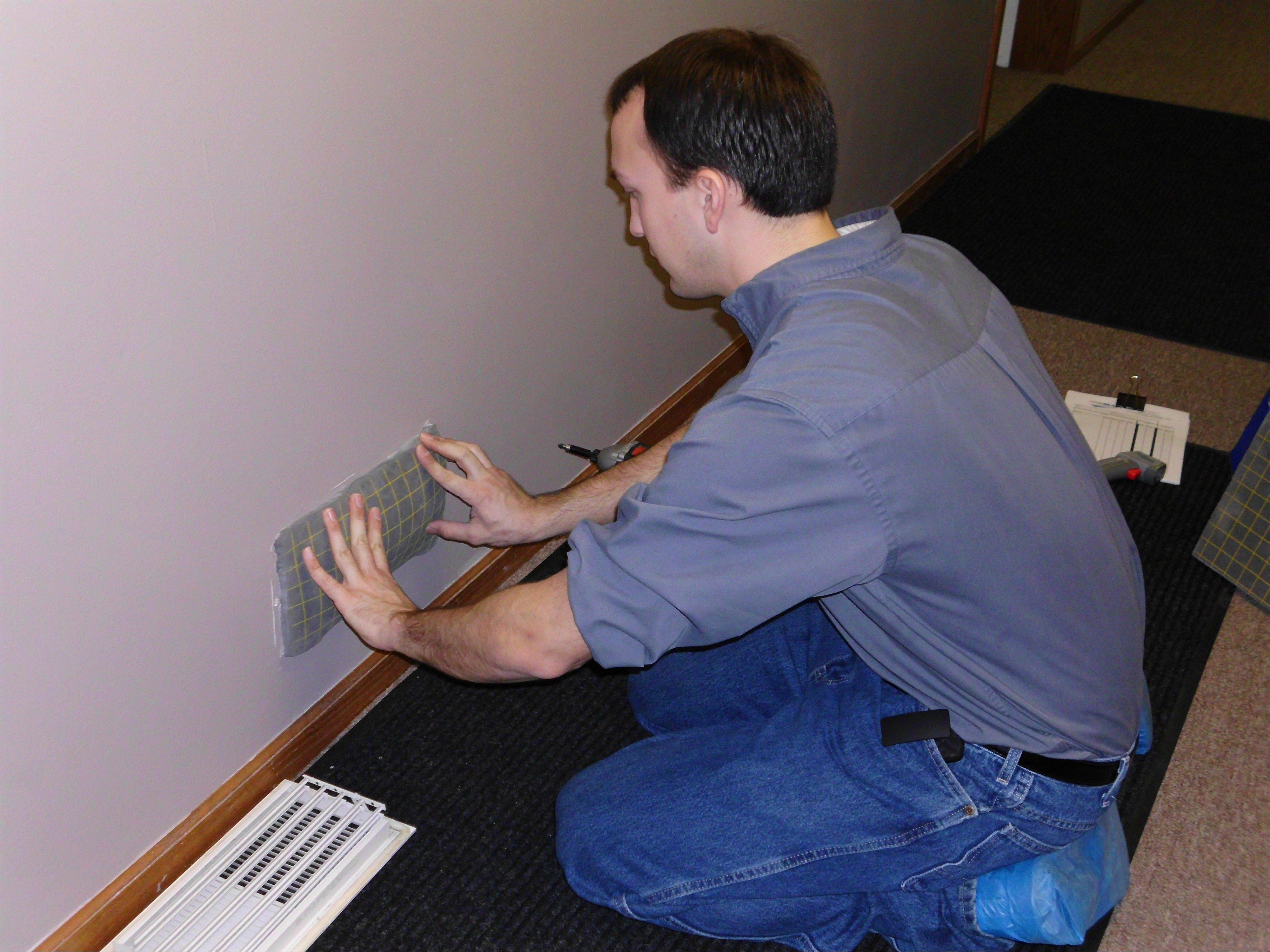 An employee of Aeroseal Solutions covers a return air vent in preparation for the sealing process.