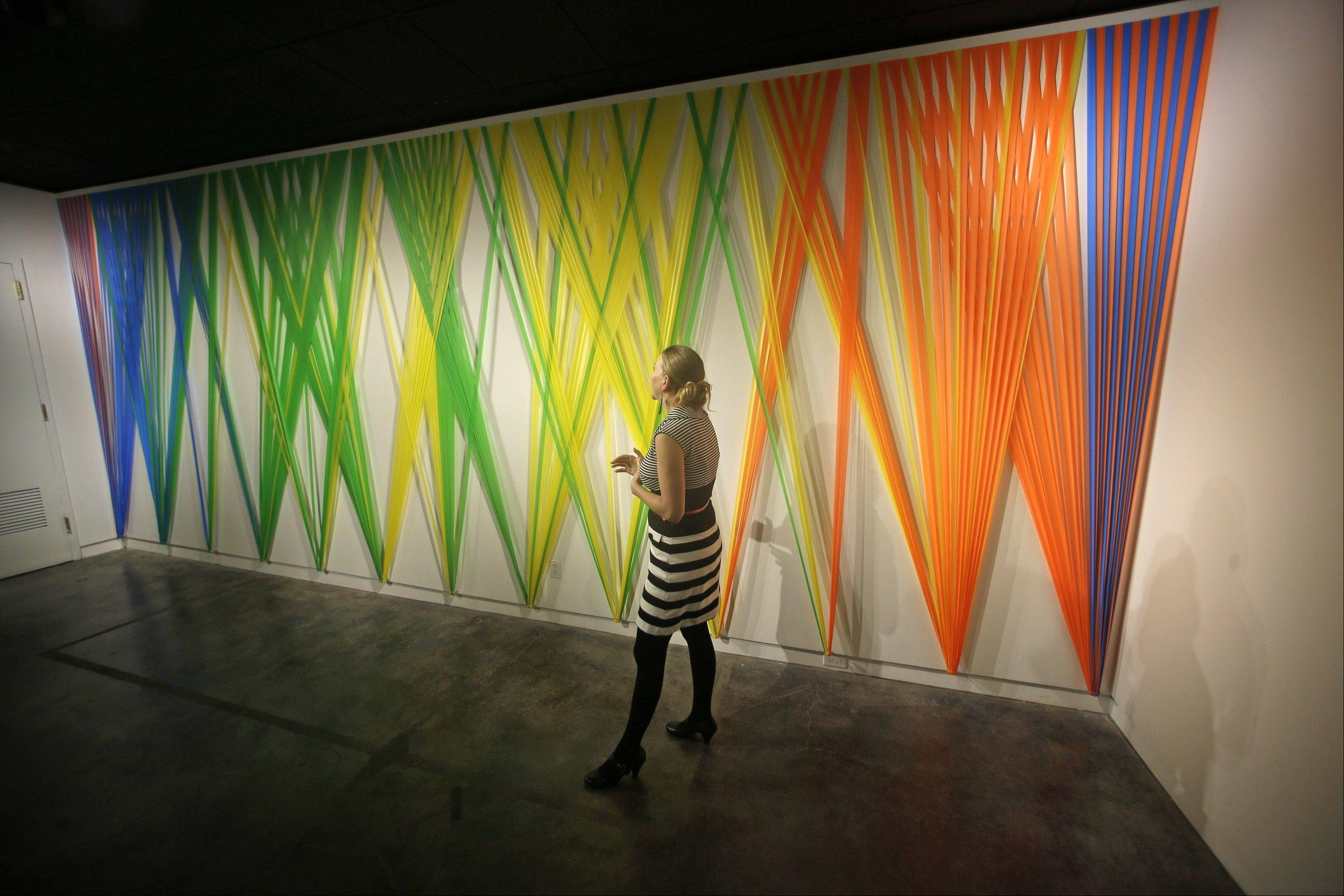Sarina Ehrgott, marketing director, walks pass the Megan Geckler exhibit at the Utah Museum of Contemporary Art.