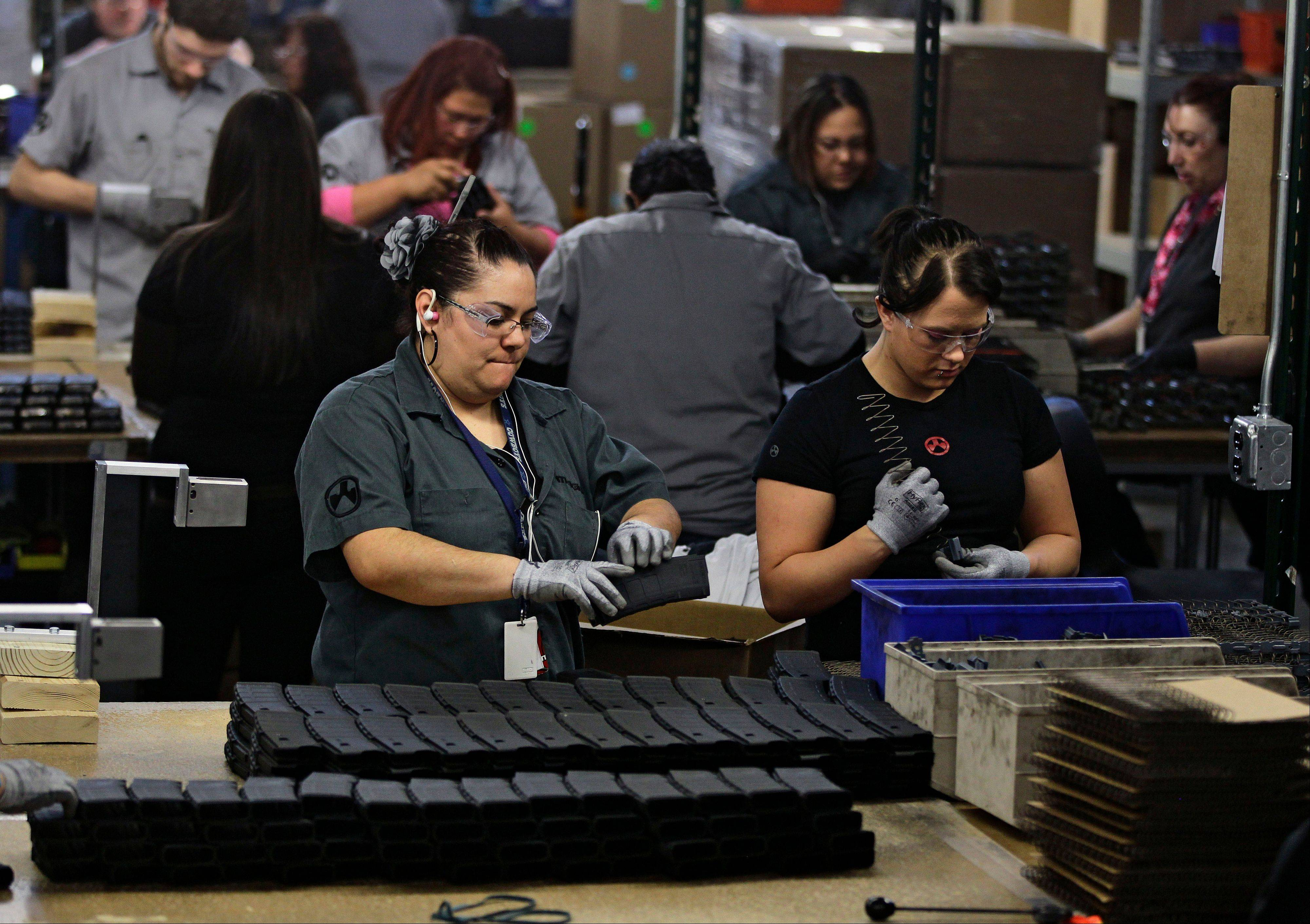 Workers assemble 30-round capacity ammunition magazines Friday for high-velocity rifles, inside the Magpul Industries plant in Erie, Colo.