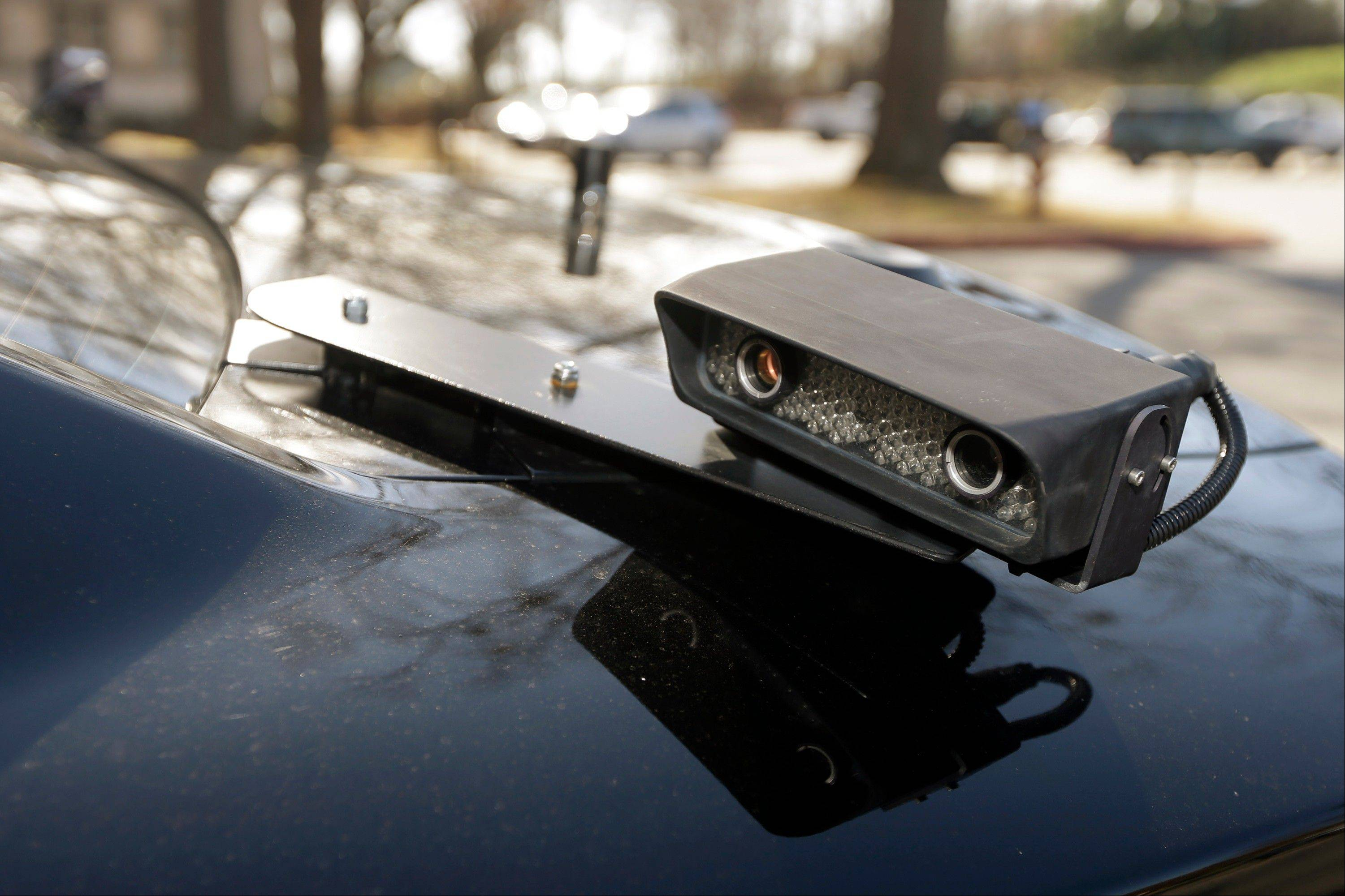A camera is mounted near the rear window of a police car in Little Rock, Ark.