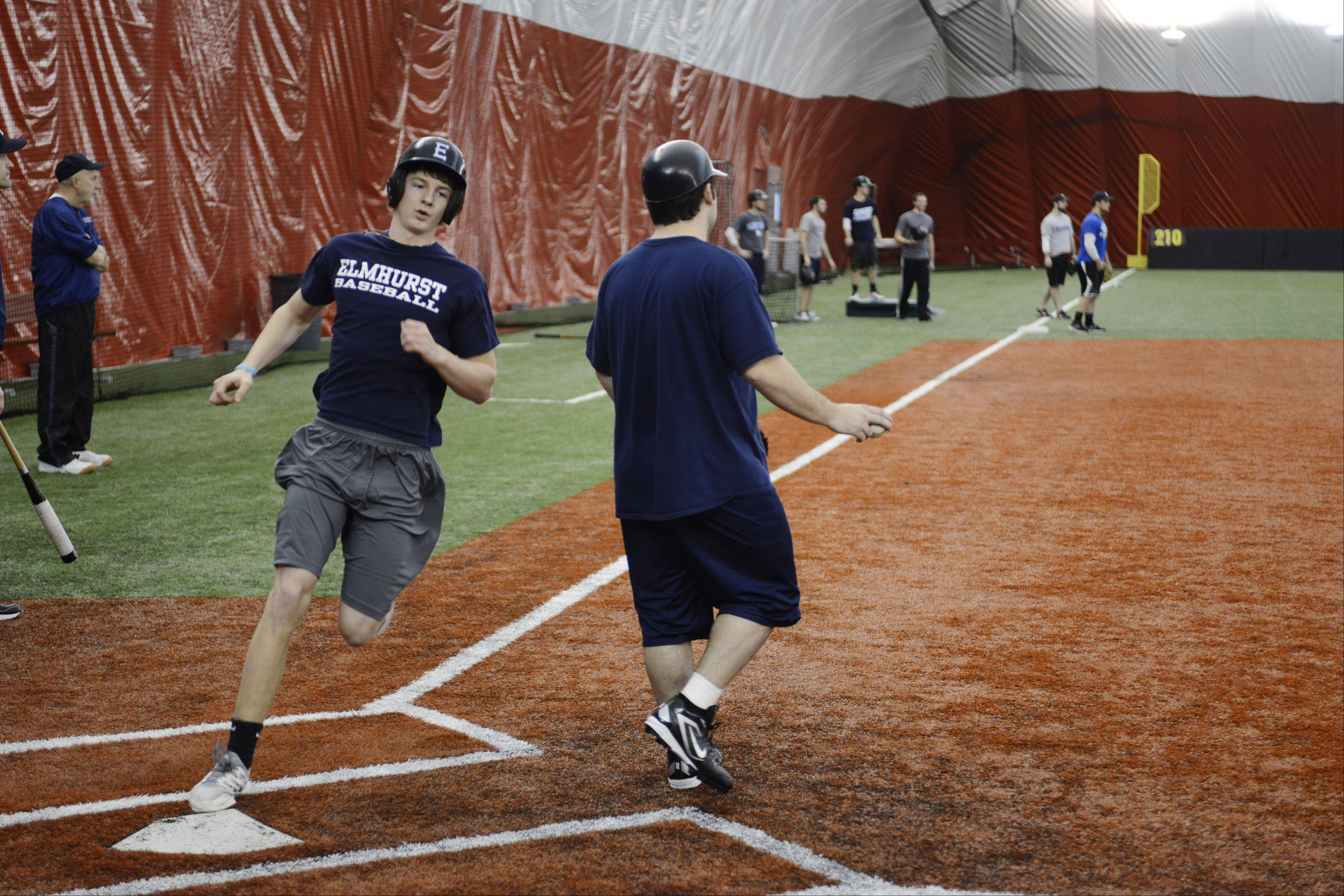 Kevin Bellew steps on the plate as catcher Zach Tsiodras awaits a throw during an Elmhurst College baseball practice at Dome at the Ballpark in Rosemont.