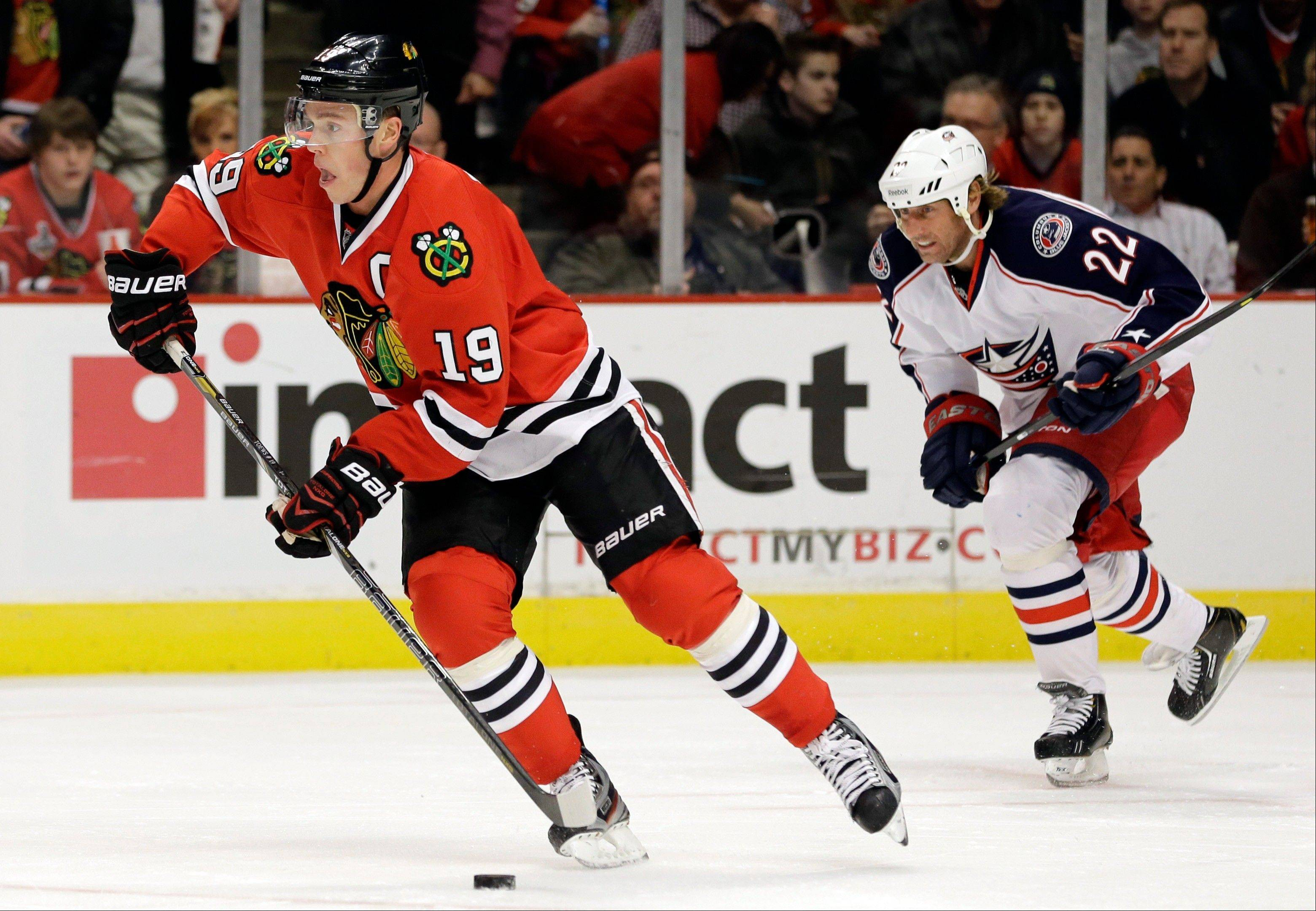 Chicago Blackhawks' Jonathan Toews, left, controls the puck past Columbus Blue Jackets' Vinny Prospal during the first period.