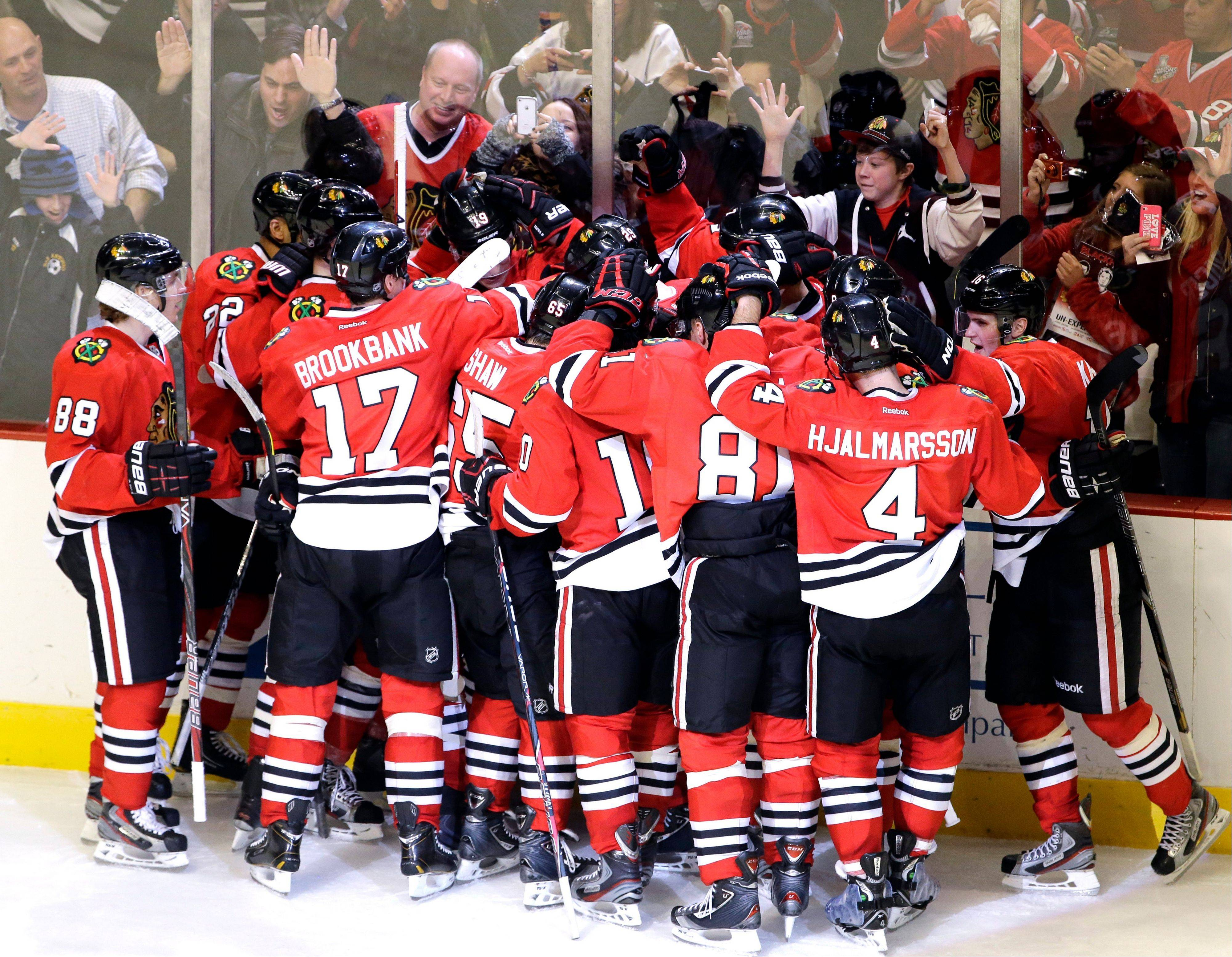 Chicago Blackhawks' Brent Seabrook celebrates with teammates after scoring his game-winning goal during overtime.