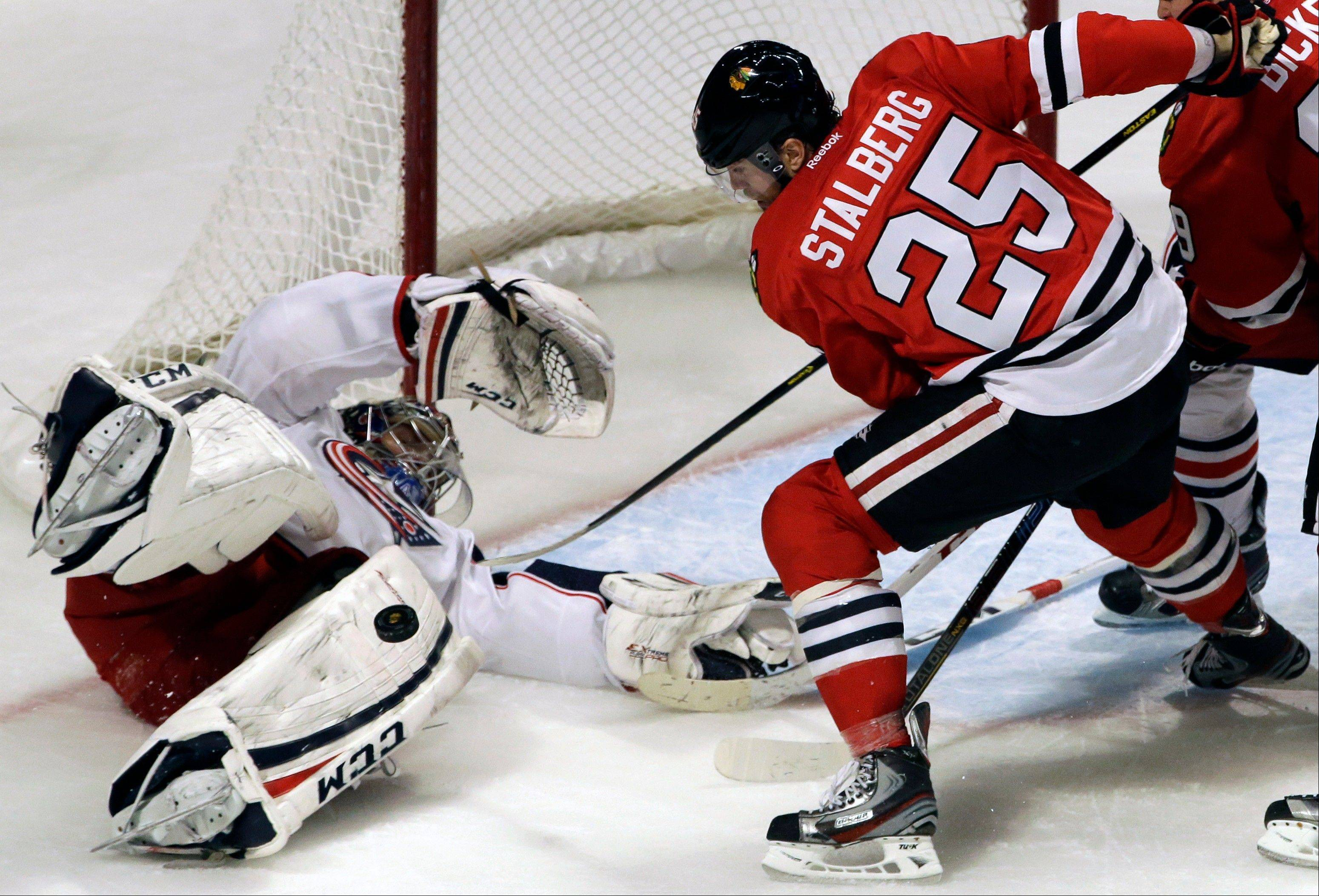 Columbus Blue Jackets goalie Steve Mason, left, blocks a shot by Chicago Blackhawks' Viktor Stalberg .