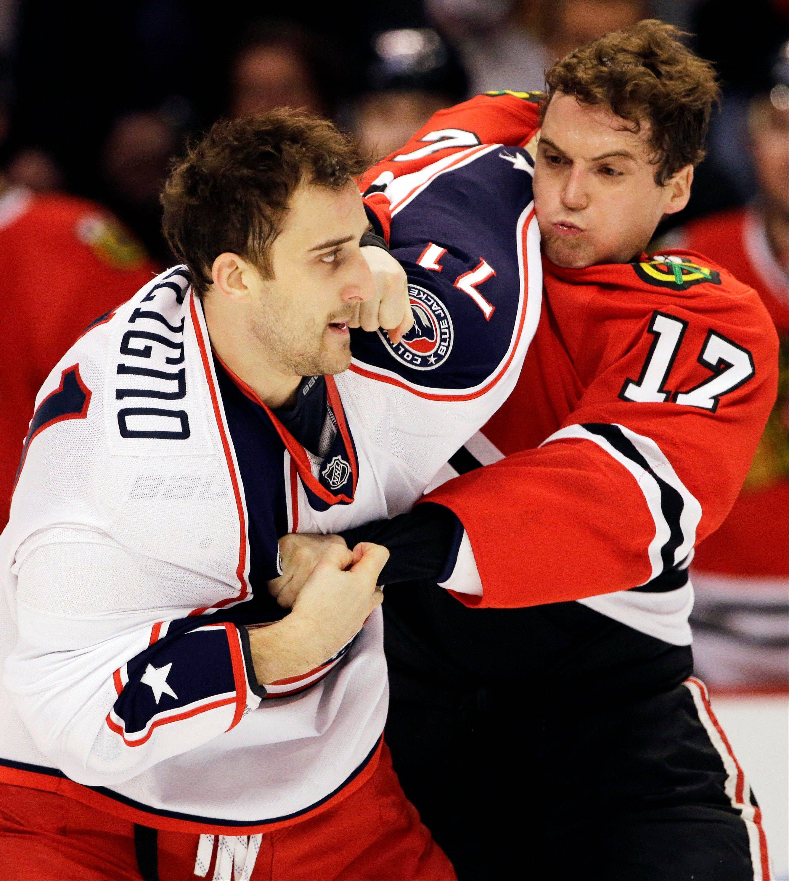 Chicago Blackhawks' Sheldon Brookbank, right, fights with Columbus Blue Jackets' Nick Foligno during the first period.