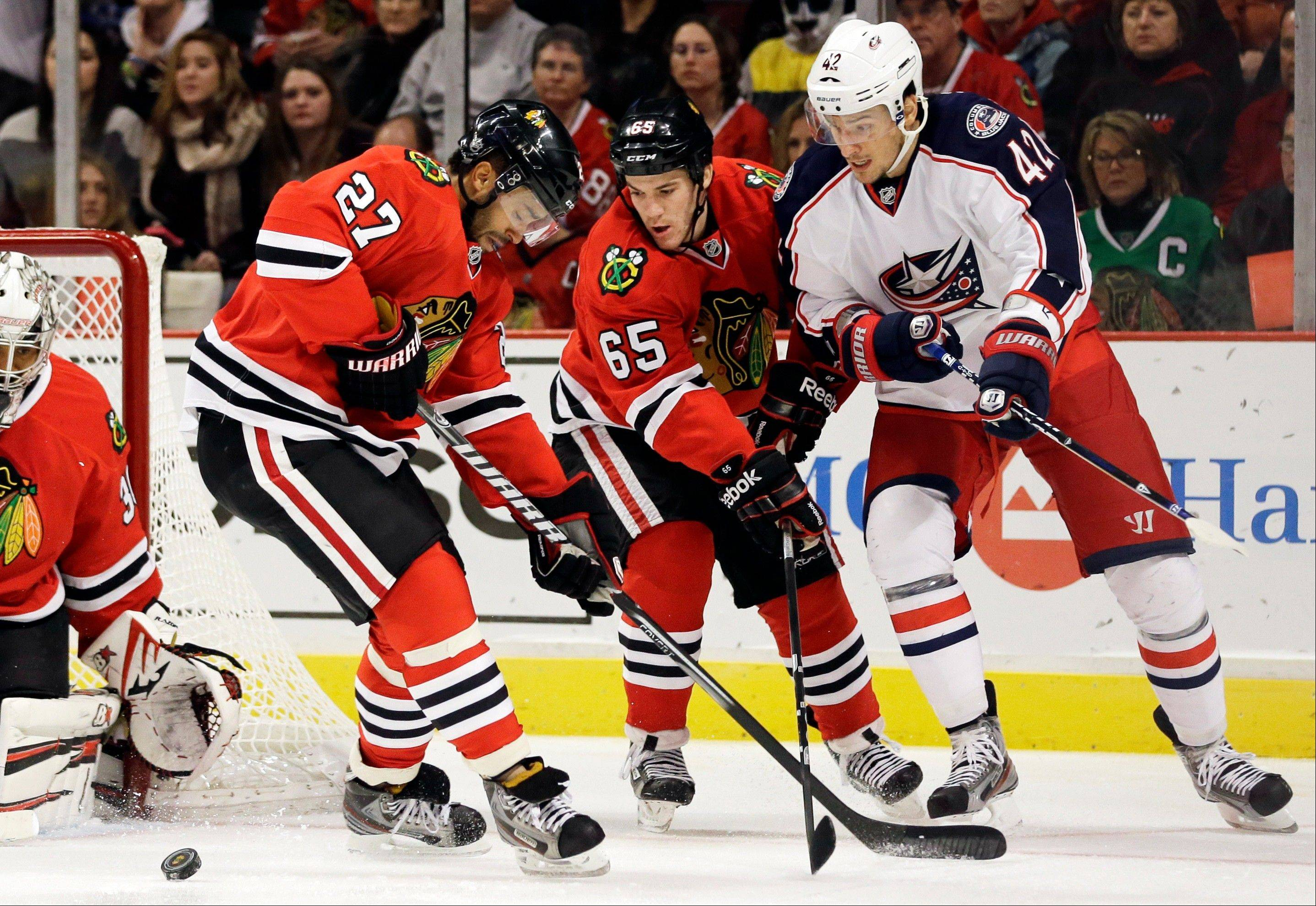 Columbus Blue Jackets' Artem Anisimov, right, battles for the puck with Chicago Blackhawks' Andrew Shaw and Johnny Oduya.
