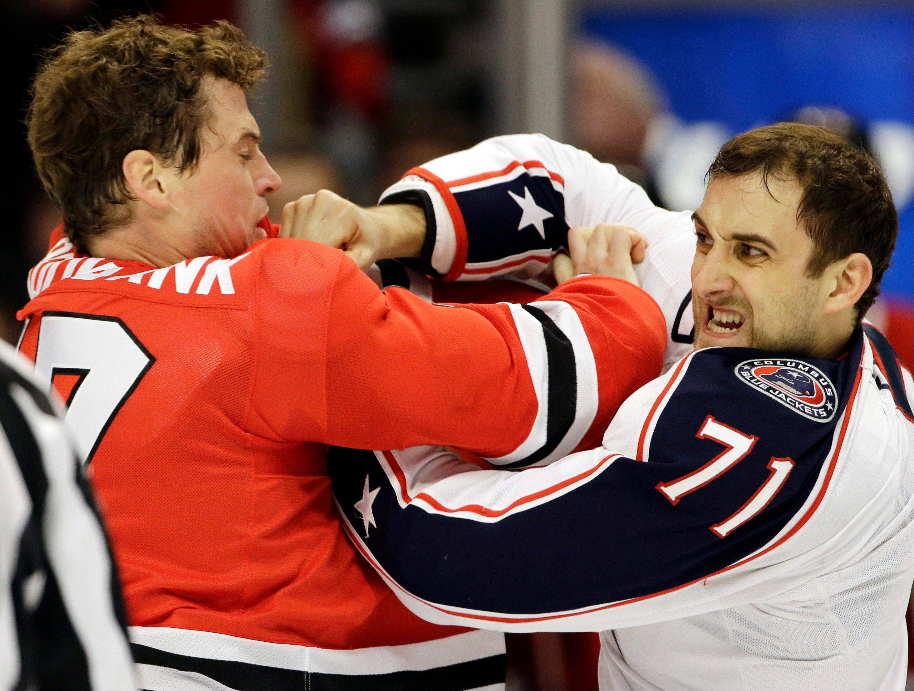 Columbus Blue Jackets' Nick Foligno, right, fights with Chicago Blackhawks' Sheldon Brookbank during the first period.