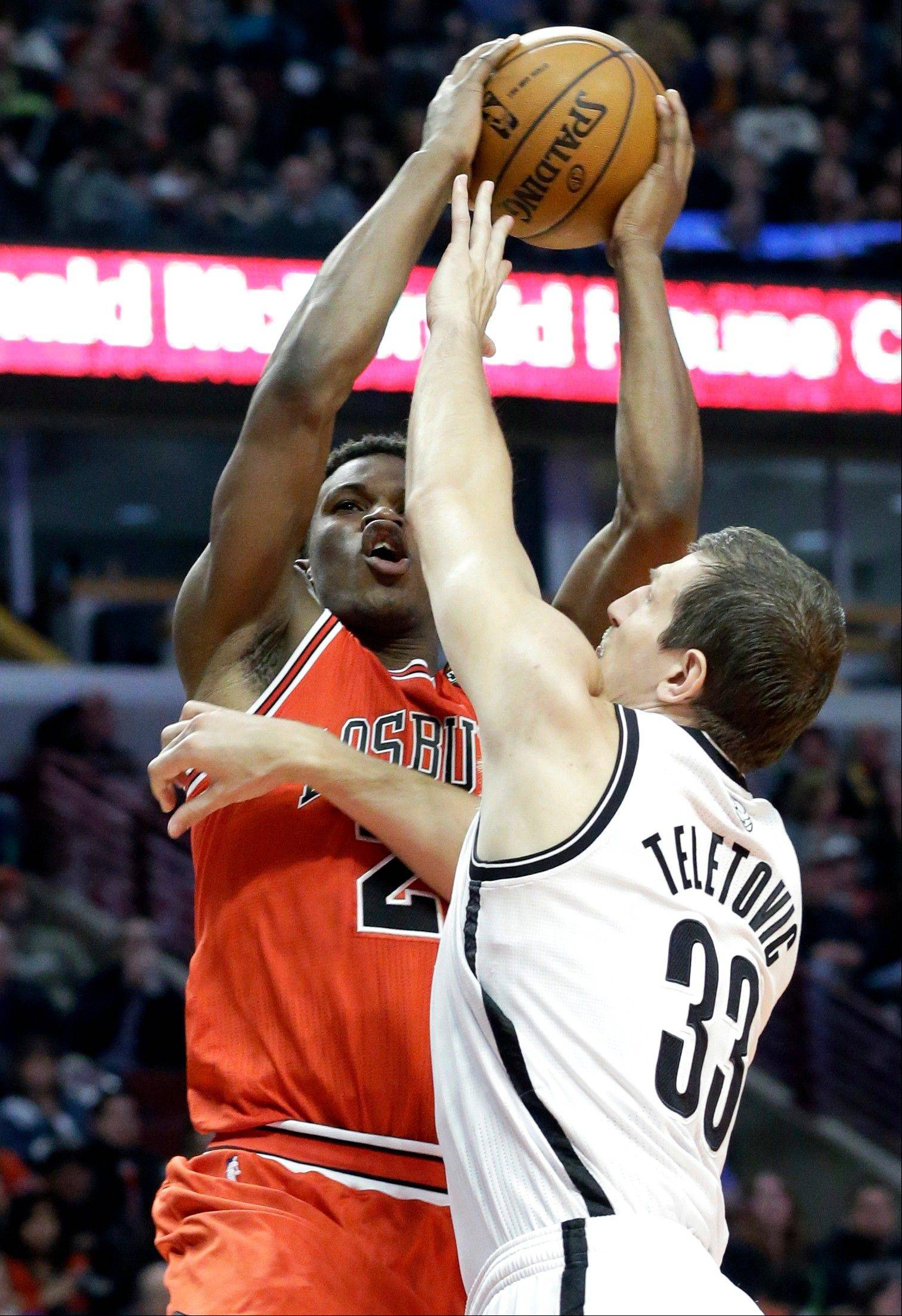 Bulls guard Jimmy Butler, left, shoots over Brooklyn Nets forward Mirza Teletovic during the second half of an NBA basketball game in Chicago on Saturday, March 2, 2013. The Bulls won 96-85.