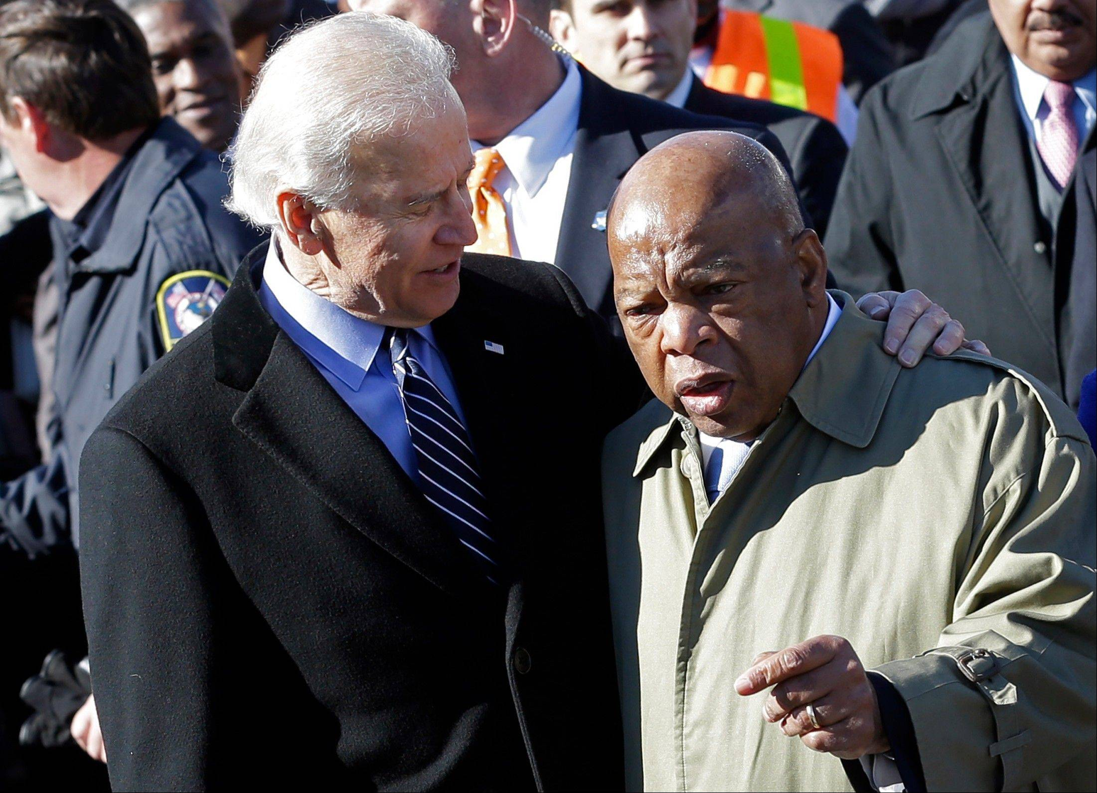 Vice President Joe Biden embraces Rep. John Lewis, as they prepare to lead a group across the Edmund Pettus Bridge in Selma, Ala., Sunday. They were commemorating the 48th anniversary of Bloody Sunday, when police officers beat marchers when they crossed the bridge on a march from Selma to Montgomery.