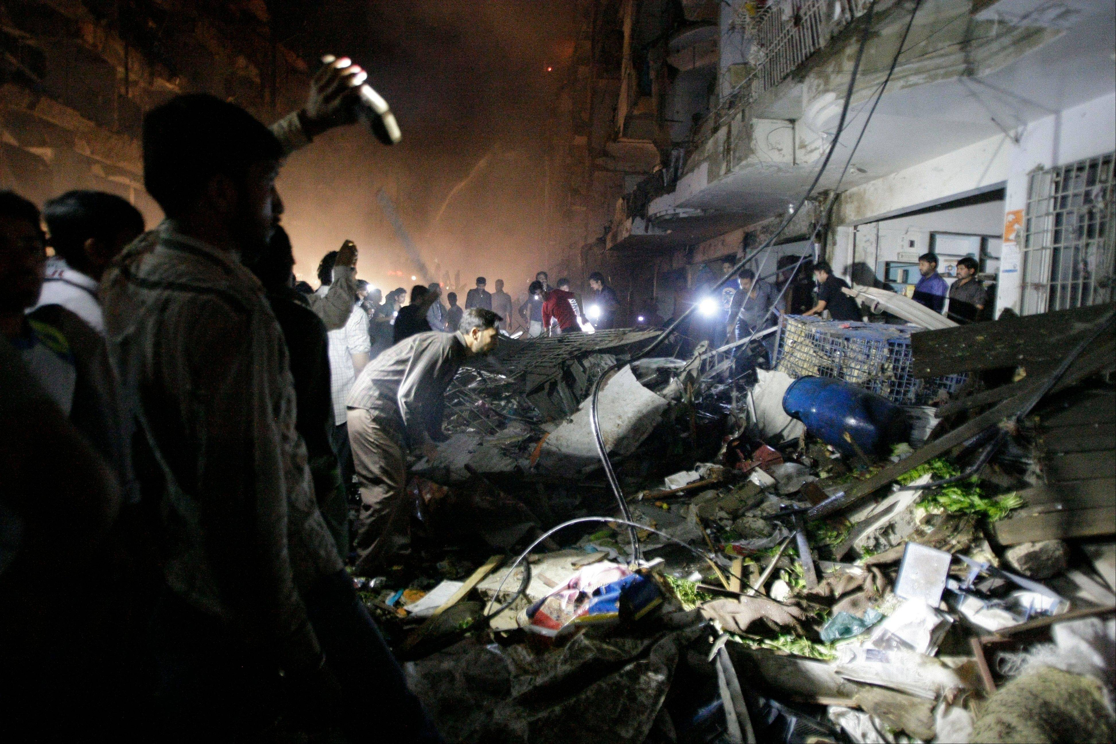 Pakistani check the site of a bomb blast in Karachi on Sunday. Pakistani officials say the bomb blast has killed dozens of people in a neighborhood dominated by Shiite Muslims.