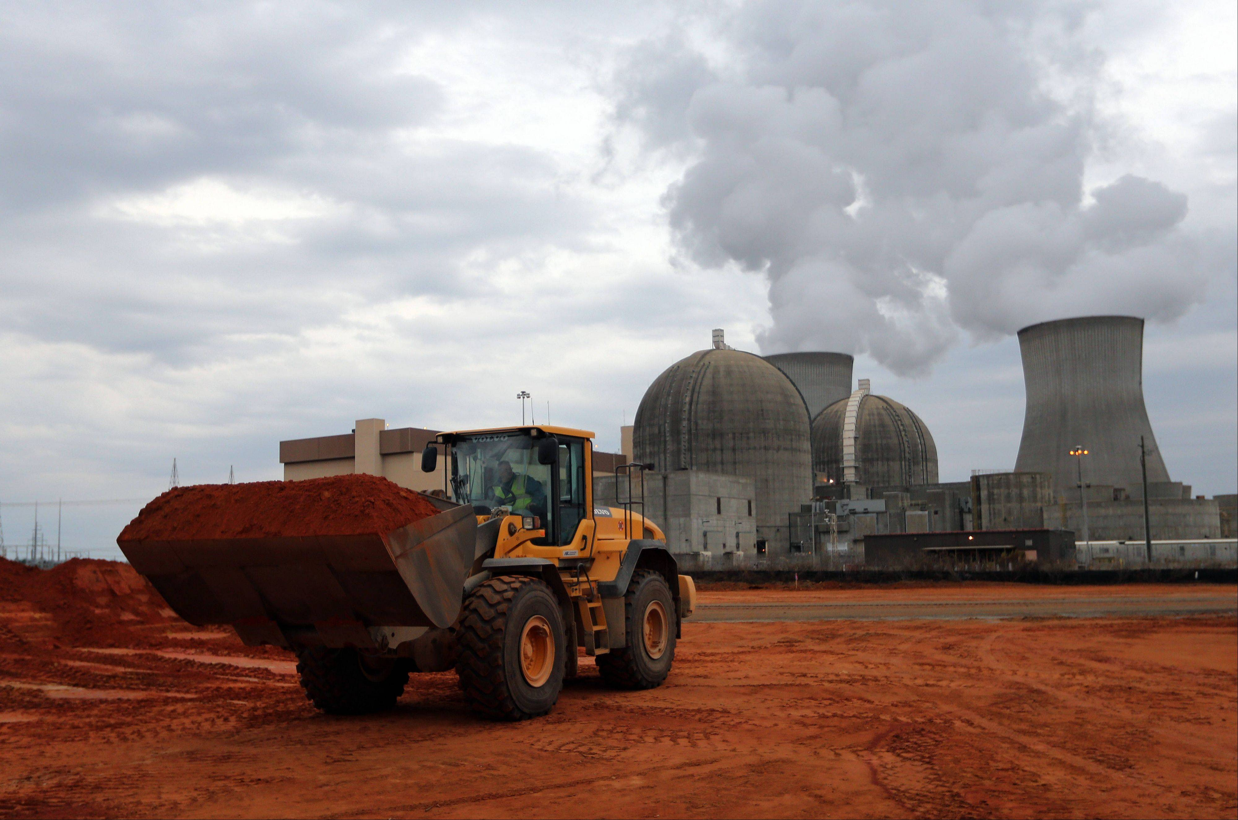 An earth mover works on a new nuclear reactor at the Plant Vogtle nuclear power plant in Augusta, Ga. One of the plant's existing reactors is shown in the background.