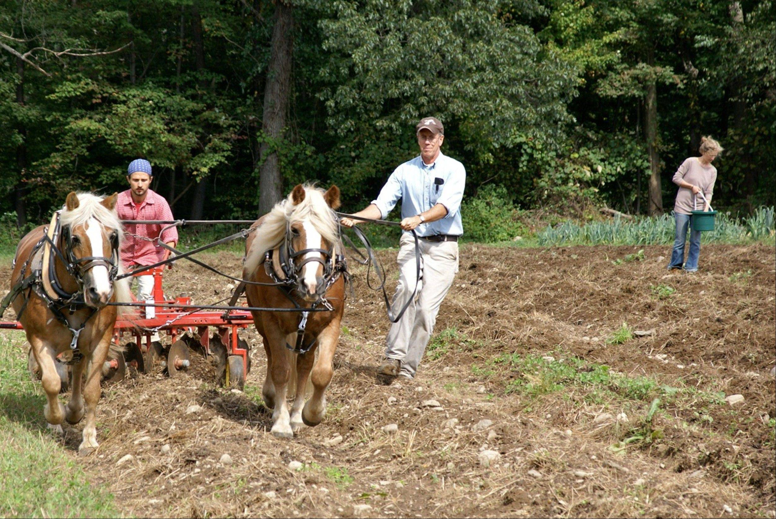 "Mac Mead, center, tills soil with horses at the Fellowship Community, a commune-like setting north of New York City. Meade, a former co-worker at the Fellowship and now director of the neighboring Pfeiffer Center agriculture school, was working with his interns in one of the gardens on the 33-acre farm, which goes beyond organic, running on ""biodynamic,"" or self-sustaining, principles."