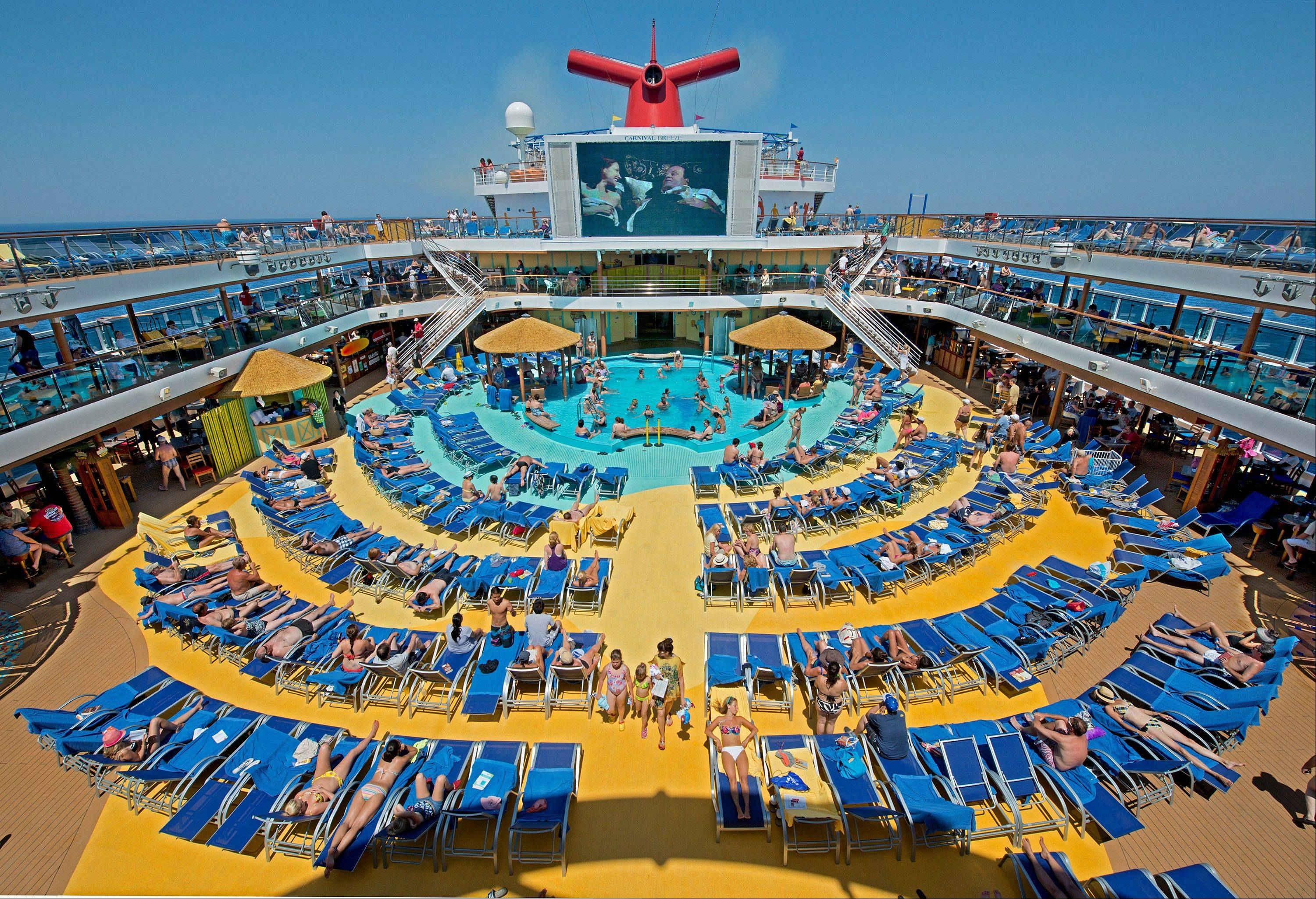 Vacationers aboard the Carnival Breeze enjoy sunbathing at sea while viewing a movie at the Carnival's Seaside Theatre, a lido deck poolside 270-square-foot LED screen offering concerts, sporting events and other programming.