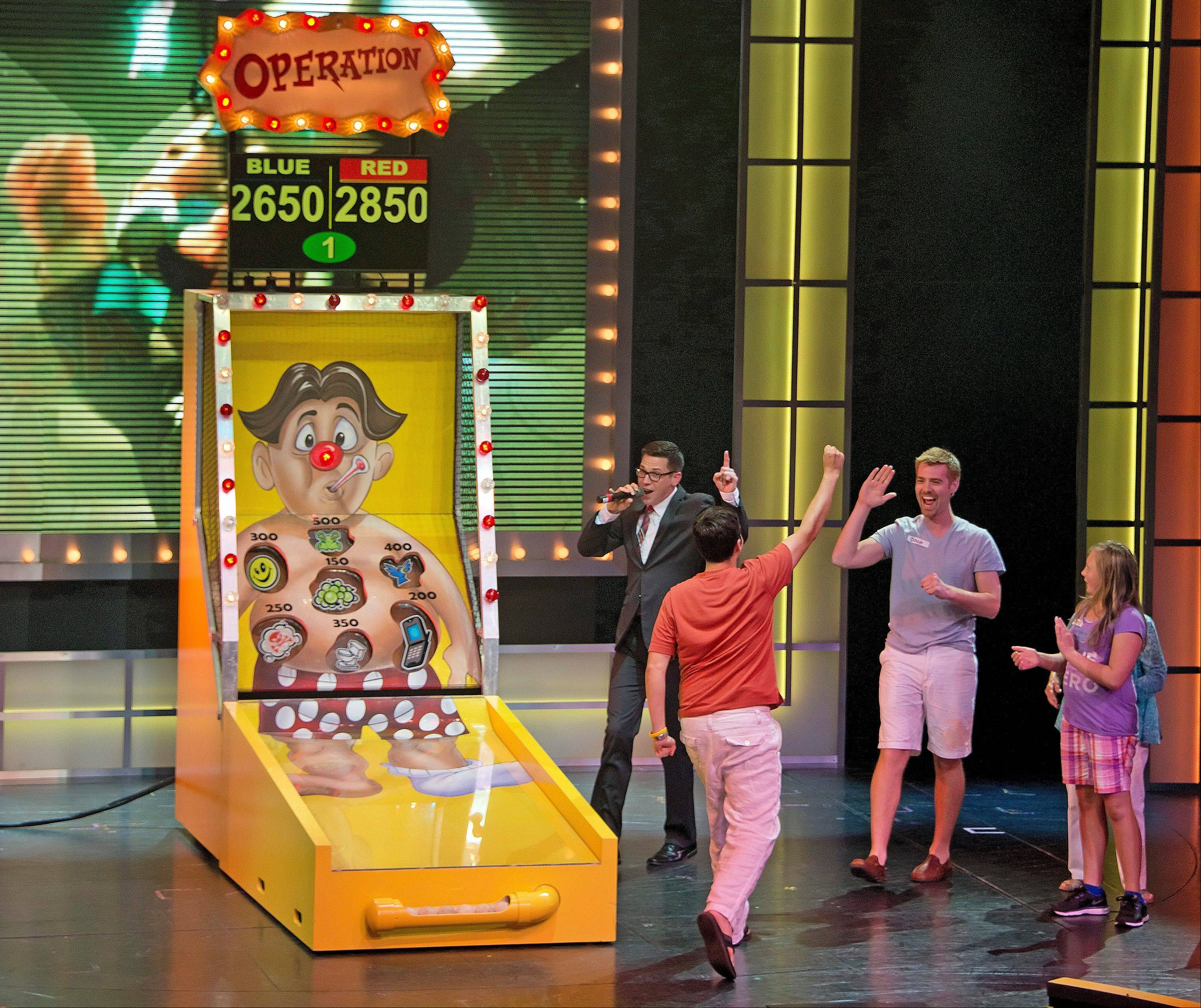 "Guests aboard the Carnival Breeze celebrate their team's victory during a giant rendition of Operation during ""Hasbro, The Game Show,"" where vacationers are part of a pretend television show through a series of larger-than-life productions."