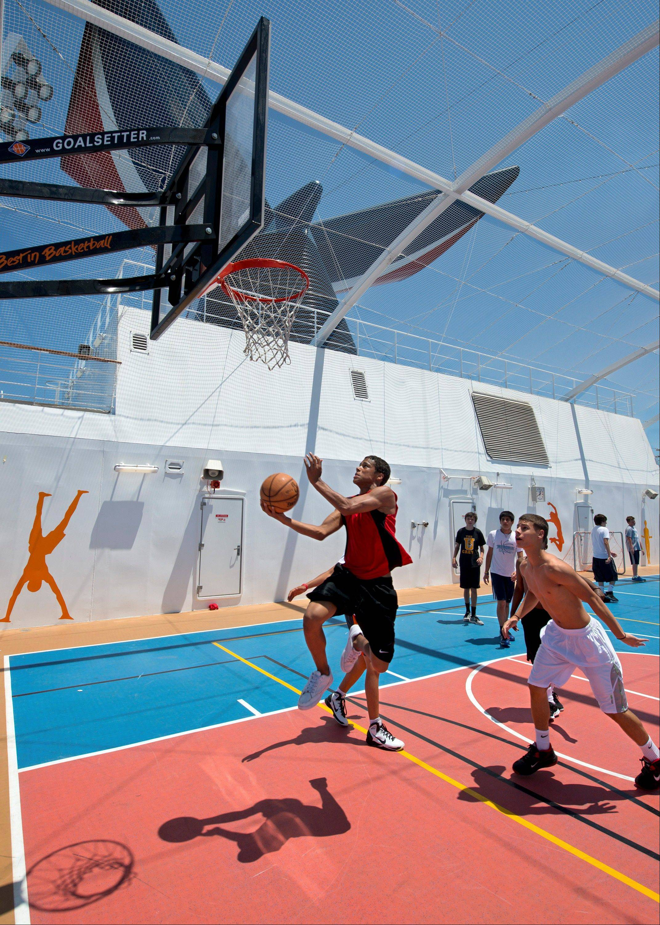 Teens on the Carnival Breeze play basketball in the ship's expansive SportSquare, an open-air recreation complex that also features a suspended ropes course, mini-golf, jogging track, ping-pong, pool, and foosball tables.