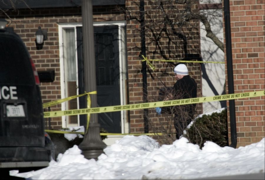 An unidentified Elgin police officer carries evidence from the scene of the city's first homicide of 2013. Police say 33-year-old Lisa Koziol-Ellis was found dead in her home early Saturday morning.