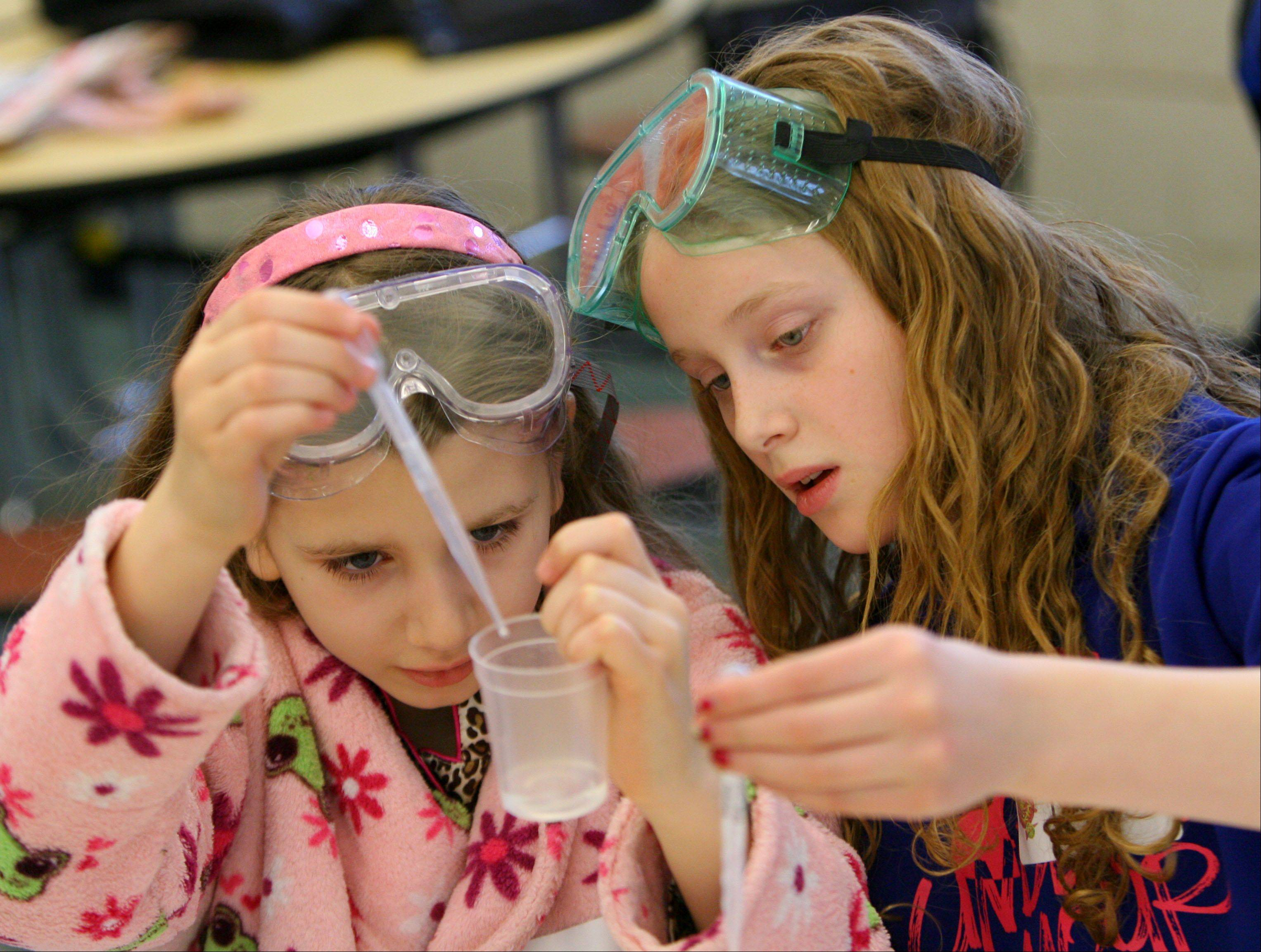 Emily Celaric, left, and Maeve Rattin measure a solution as Copeland Manor fifth graders conduct chemistry experiments with parent volunteers Thursday in Libertyville.