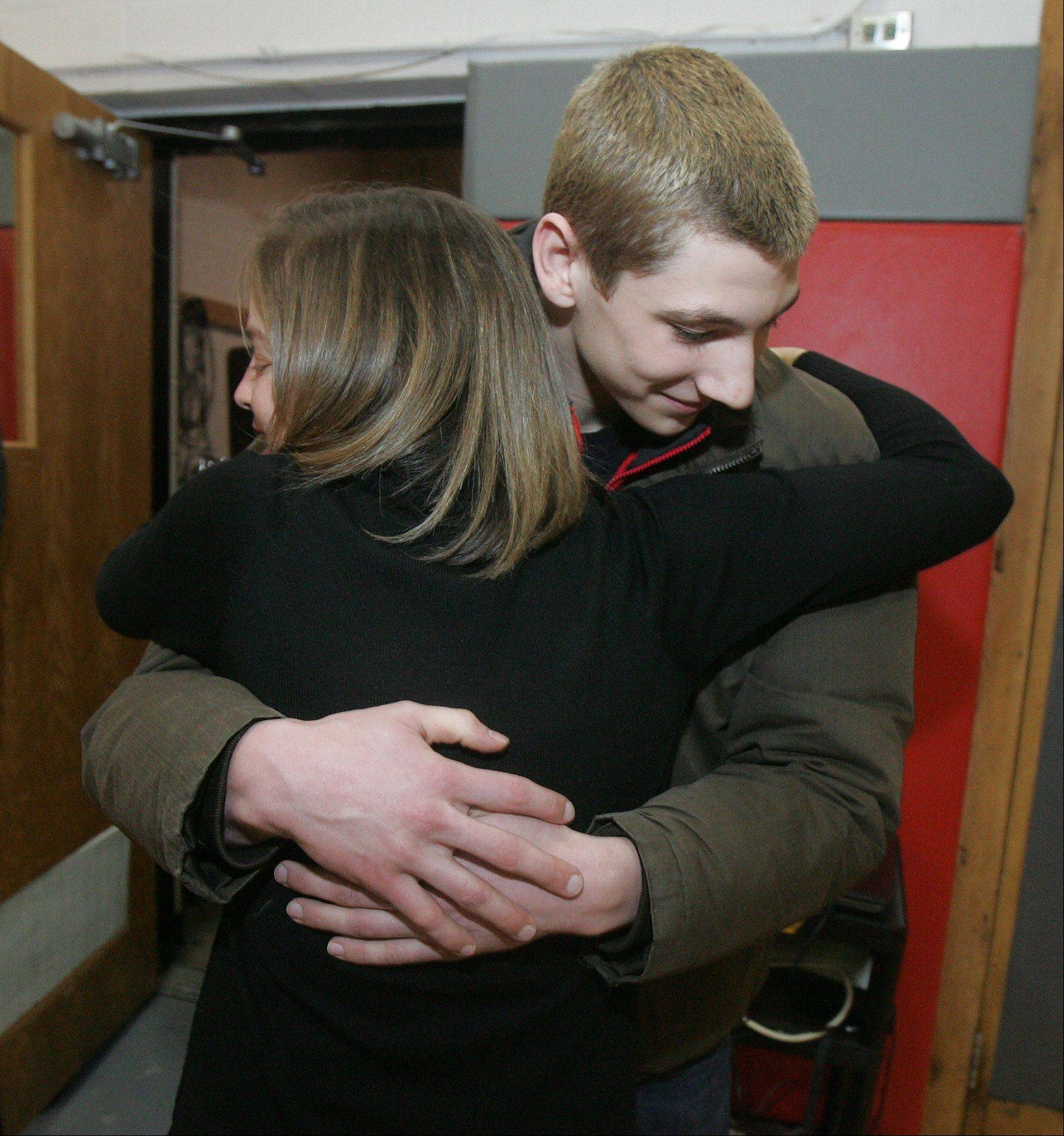Principal Lauren Fagel hugs swimmer Connor Black who was honored at an all-school assembly Wednesday at Mundelein High School after he broke state and national records at the state swimming tournament. Connor set a state record in the 50 freestyle and broke state and national records in the 100 butterfly.