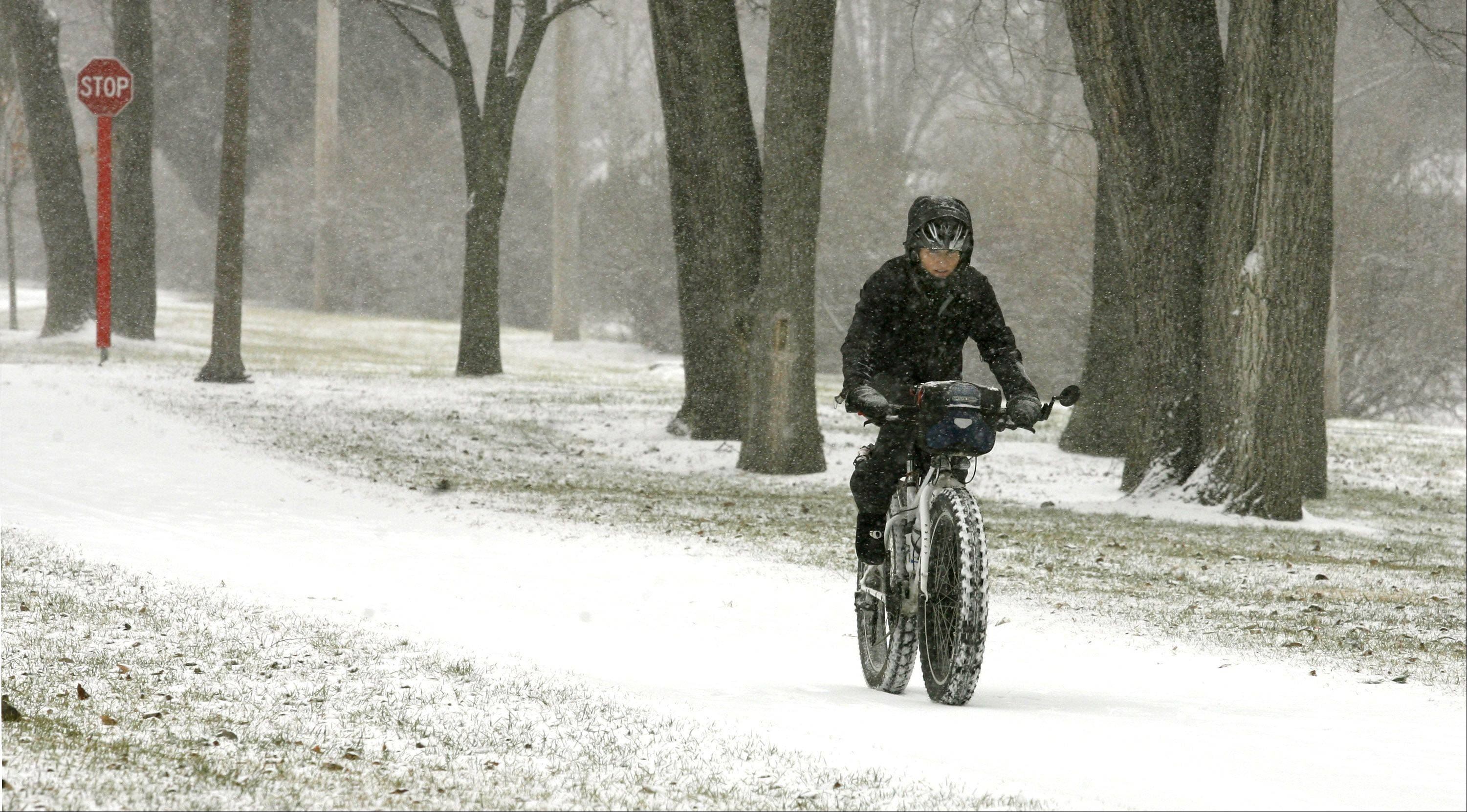 A lone bicycle rider makes her way east through a light dusting of snow along the Illinois Prairie Path in Villa Park. I used a long lens to compresses the subject, framed between banks of trees. A blood-red stop sign accents the monochromatic feel.