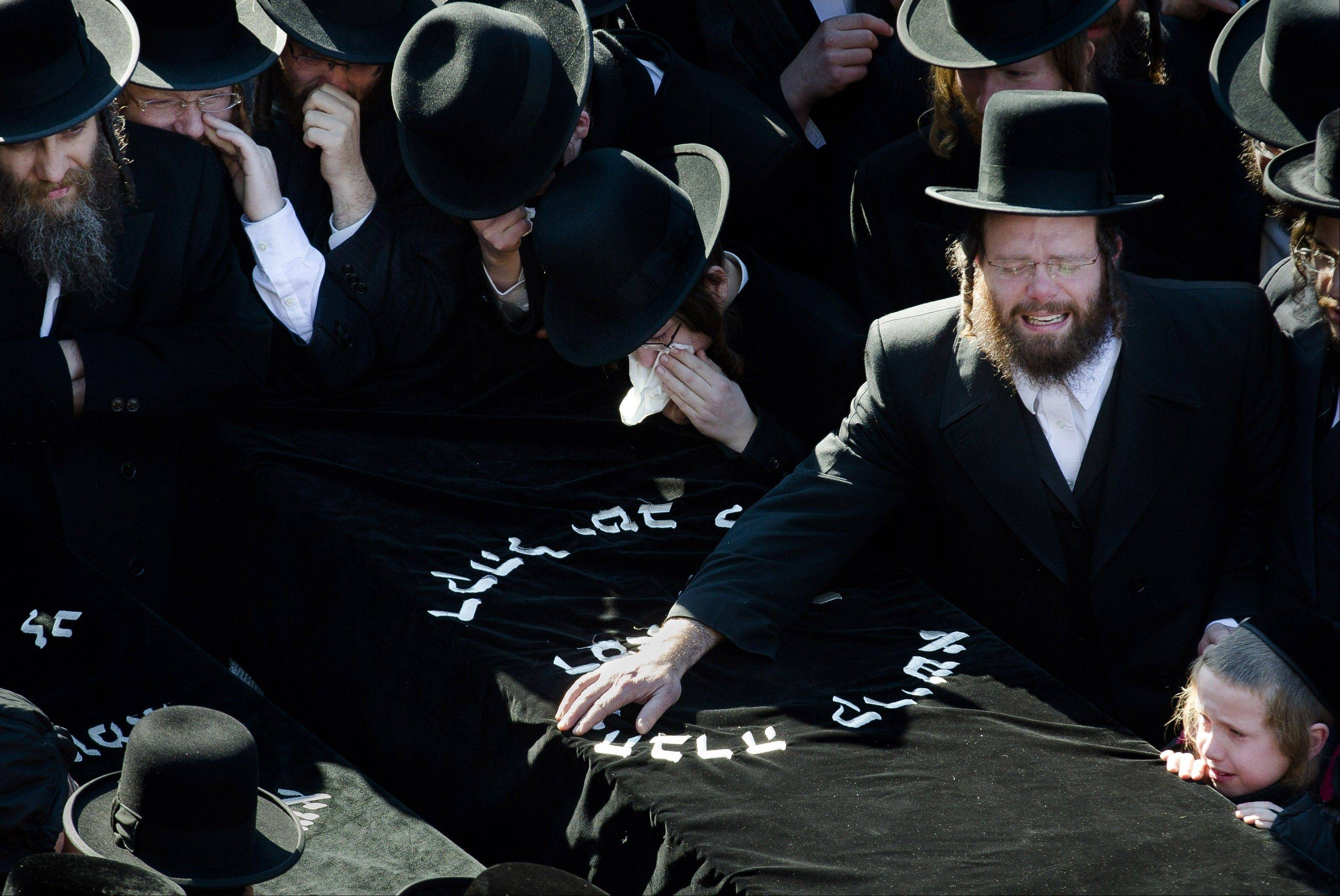 Members of the Satmar Orthodox Jewish community grieve over the coffins at the funeral for two expectant parents who were killed in a car accident Sunday in the Brooklyn borough of New York. A driver struck the car early Sunday morning, killing both parents. Their baby, who was born prematurely, died early Monday morning.