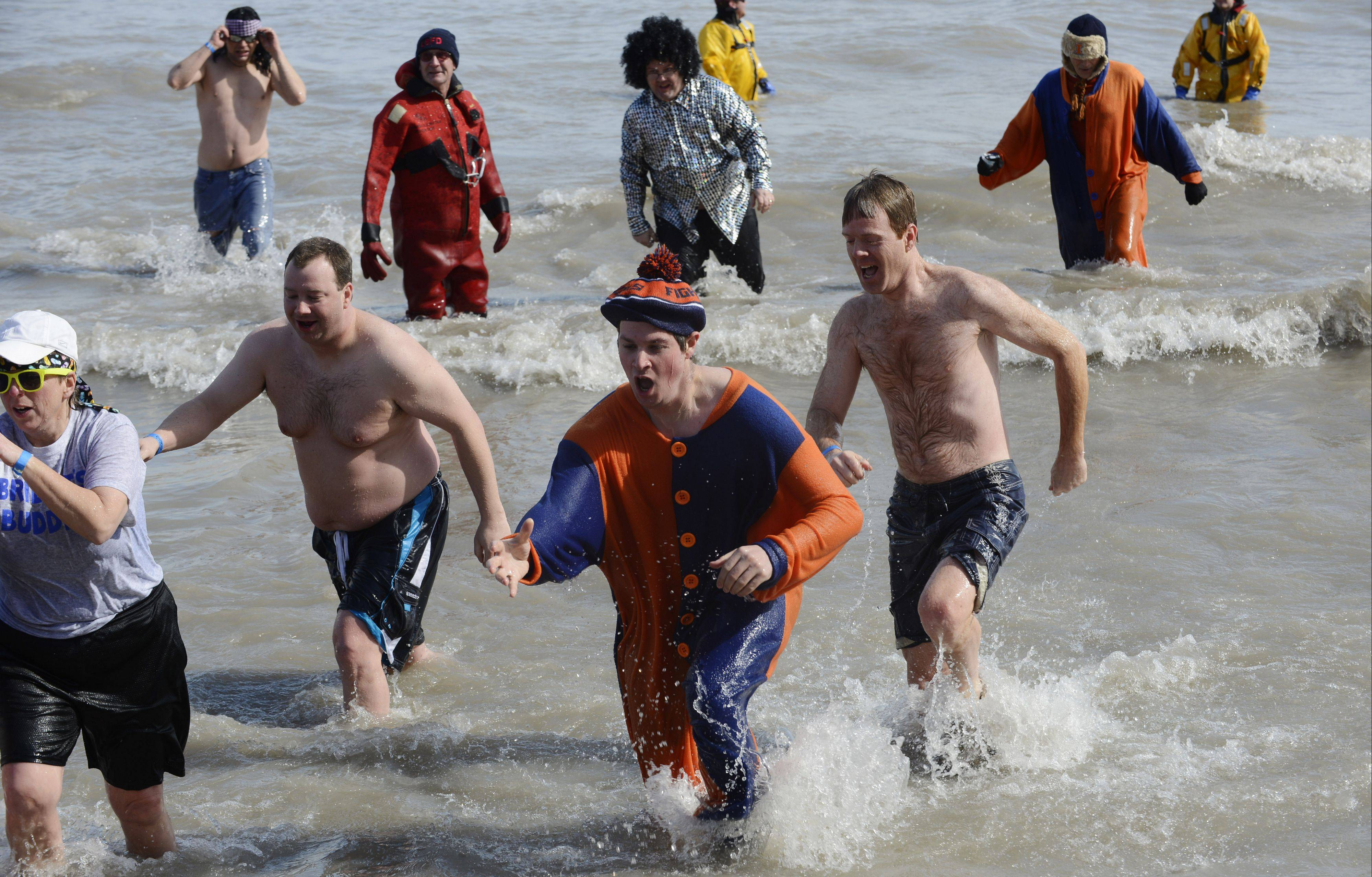 Event participants exit the icy waters on Saturday of Lake Michigan during the Law Enforcement Torch Run Polar Plunge at Sunrise Beach in Lake Bluff.