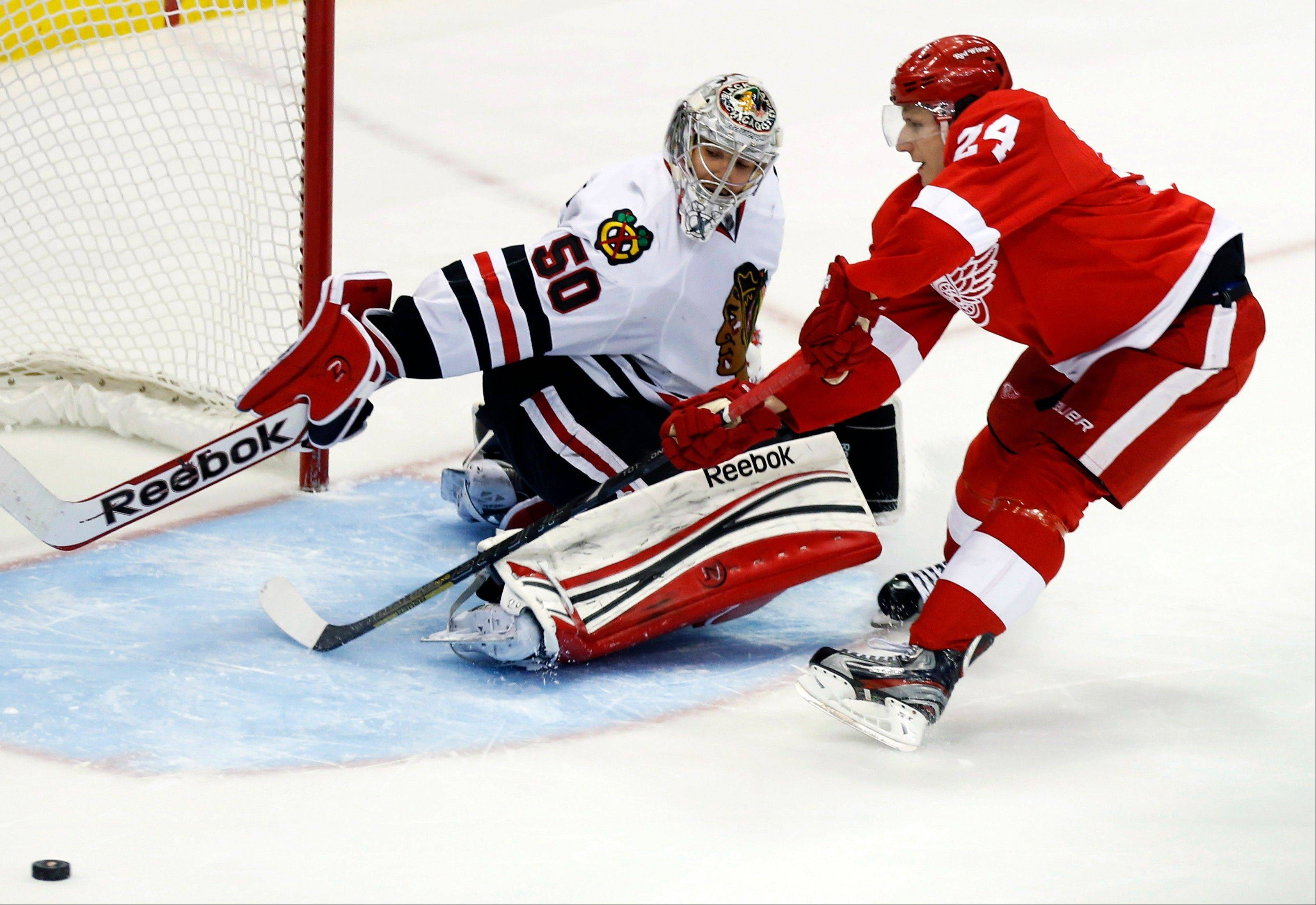 Blackhawks goalie Corey Crawford (50) deflects a shot by Detroit Red Wings center Damien Brunner (24) during the shootout of an NHL hockey game, Sunday, March 3, 2013, in Detroit. The Blackhawks won 2-1.