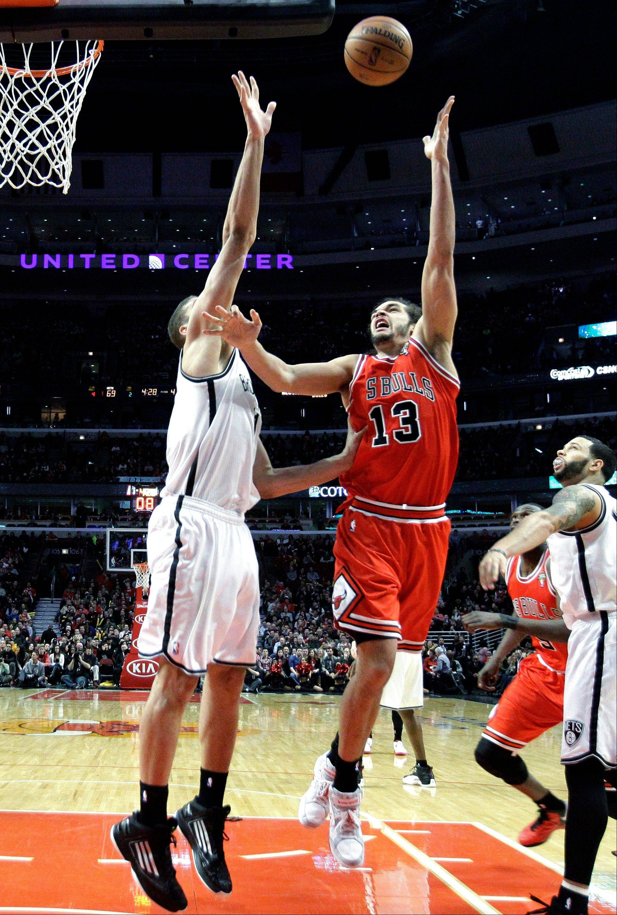 Joakim Noah, right, shoots over Brooklyn Nets center Brook Lopez during the second half Saturday at the United Center. Noah has played 86 minutes in the Bulls' last two games, and the team has another contest Sunday.