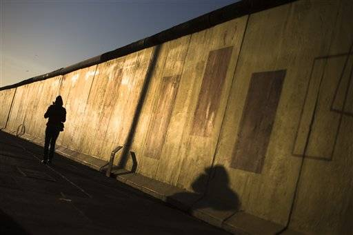 In early morning light a protester walks alongside the East Side Gallery named section of the former Berlin Wall in Berlin, Monday, March.