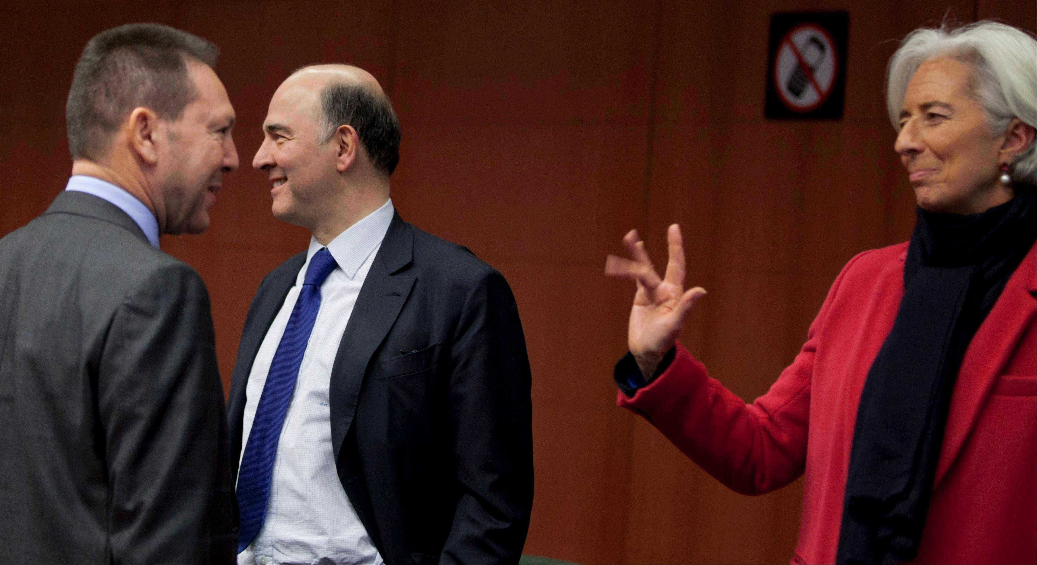 Managing Director of the International Monetary Fund Christine Lagarde, right, waves to Greek Finance Minister Yannis Stournaras, left, and French Finance Minister Pierre Moscovici during a meeting of eurogroup finance ministers in Brussels on Monday.