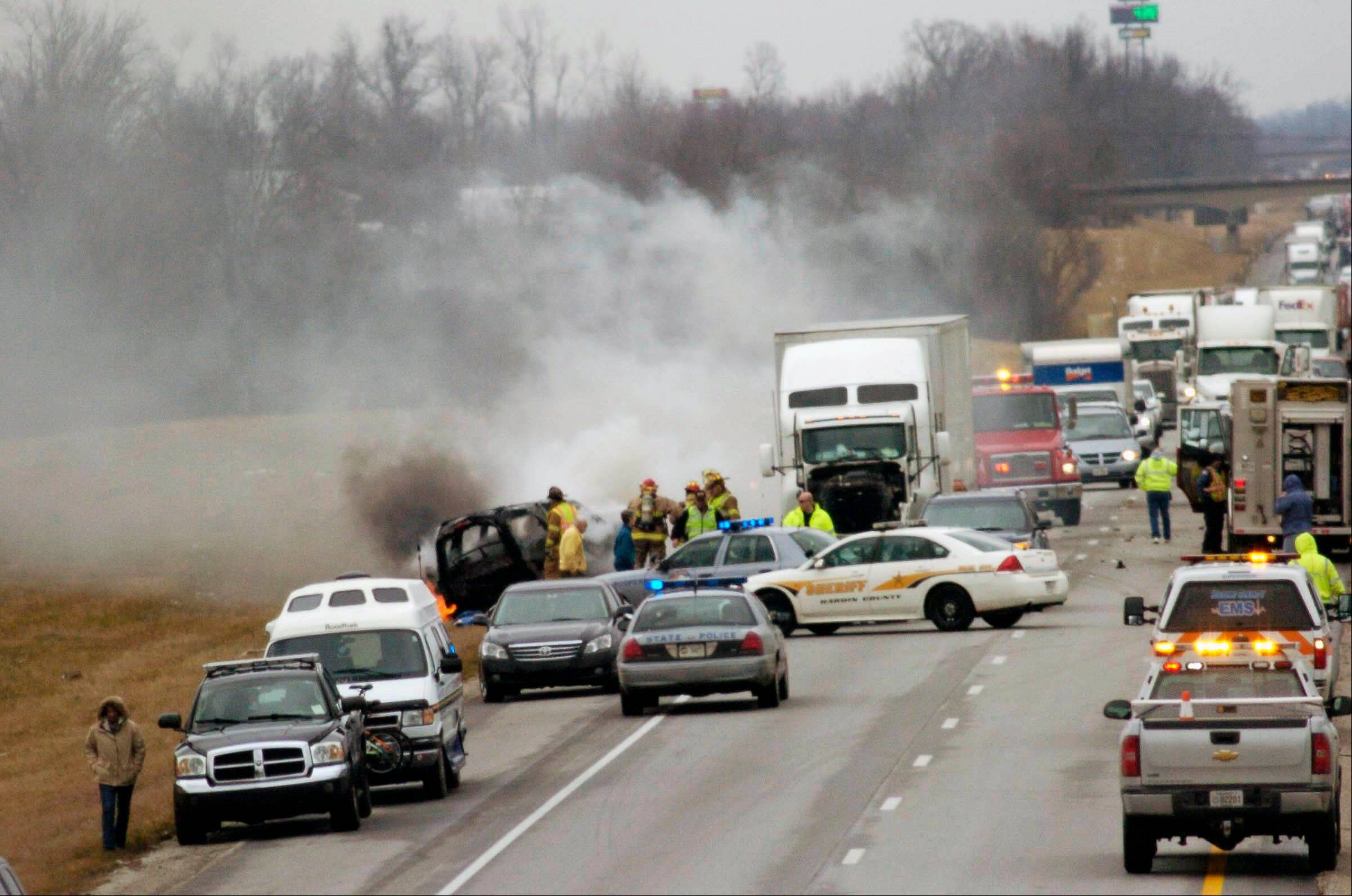 Emergency personnel work at the scene of a multivehicle wreck on Interstate 65, Saturday, north of Sonora, Ky. Kentucky State Police say six people are dead in two crashes that happened near the same location in central Kentucky on Interstate 65.