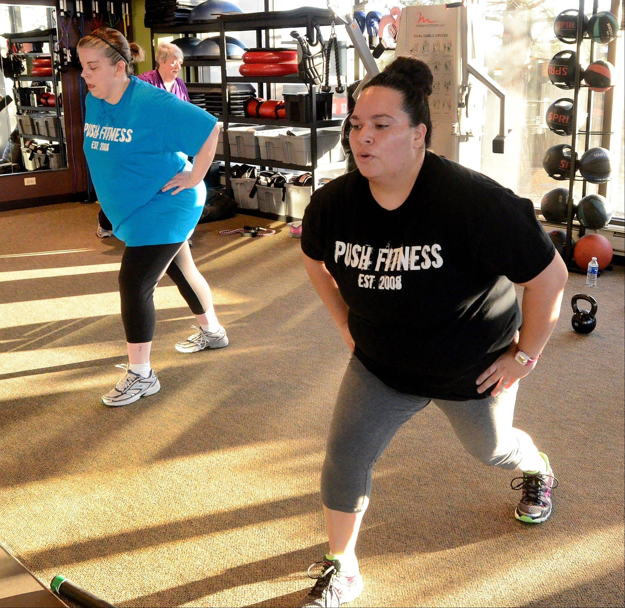 Marianne Costales-Roman, right, works out next to the Daily Herald's Fittest Loser Melynda Findlay.