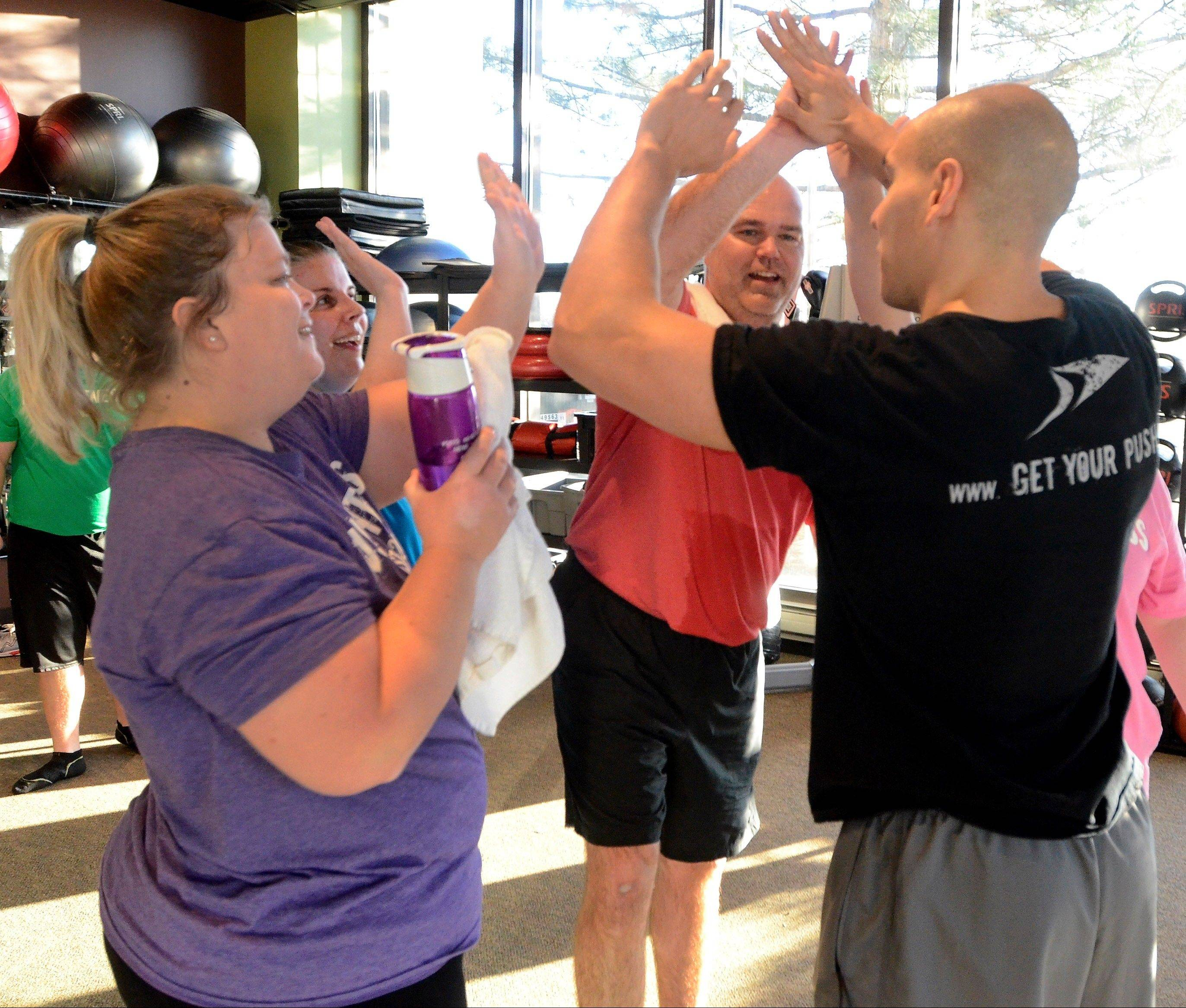 It's high-fives all around with trainer Tony Rinhart at the end of the 45-minute boot-camp workout.