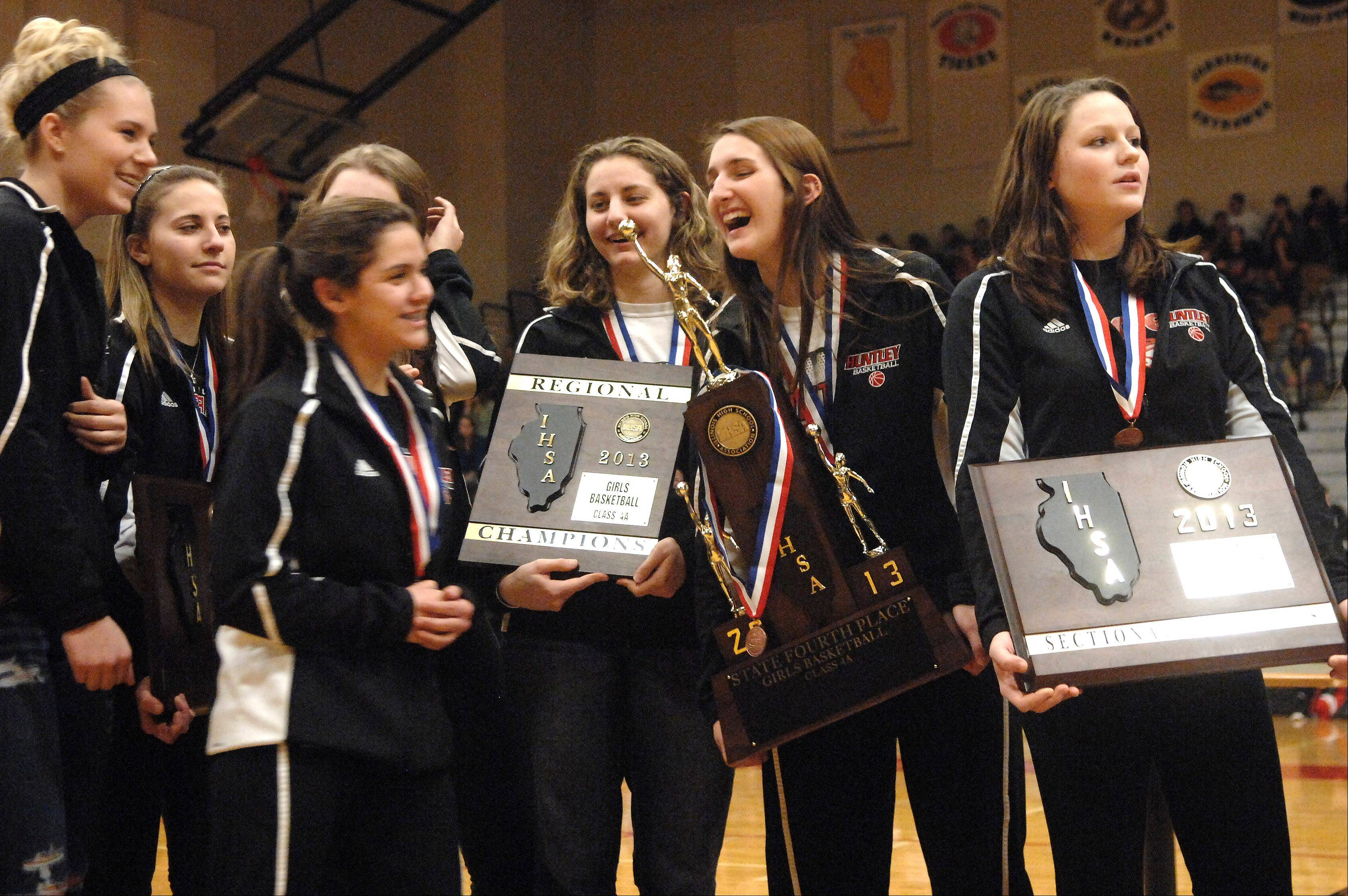 Huntley High School basketball players show off their hardware during a pep assembly Monday. The Red Raiders finished fourth in the state basketball tournament last weekend.