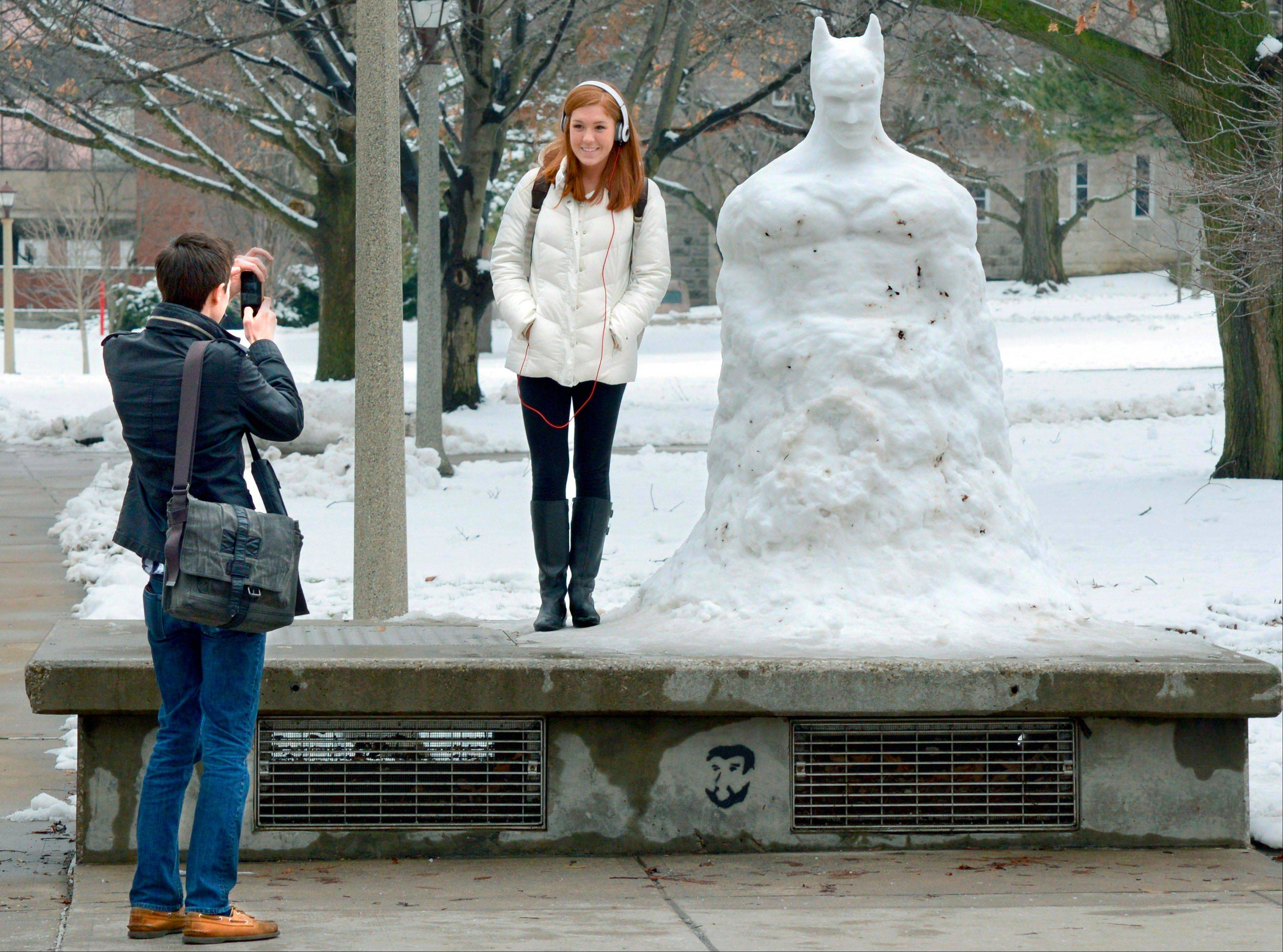 Jonathon Napiorkowski of Gurnee, a junior at Illinois State University, photographs Anna Templin, a junior from Hagerstown, Ind., by a large snow sculpture of Batman that has been drawing a large following on the ISU quadrangle in Normal.