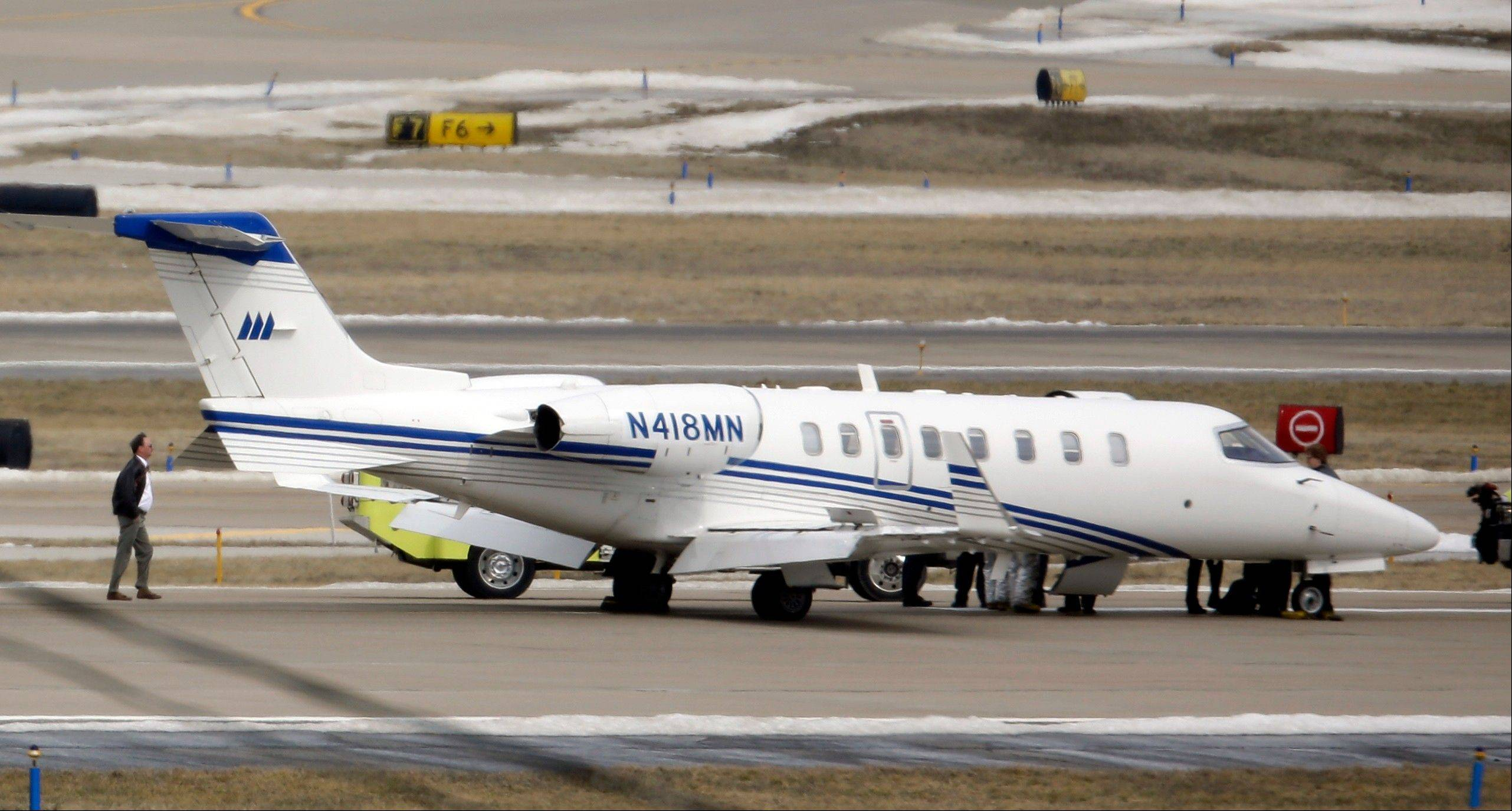 An aircraft sits on the tarmac after making an emergency landing at Lambert St. Louis International Airport Monday in St. Louis. An official said the eight passengers aboard the small aircraft with landing gear troubles walked off the plane after it landed safely.