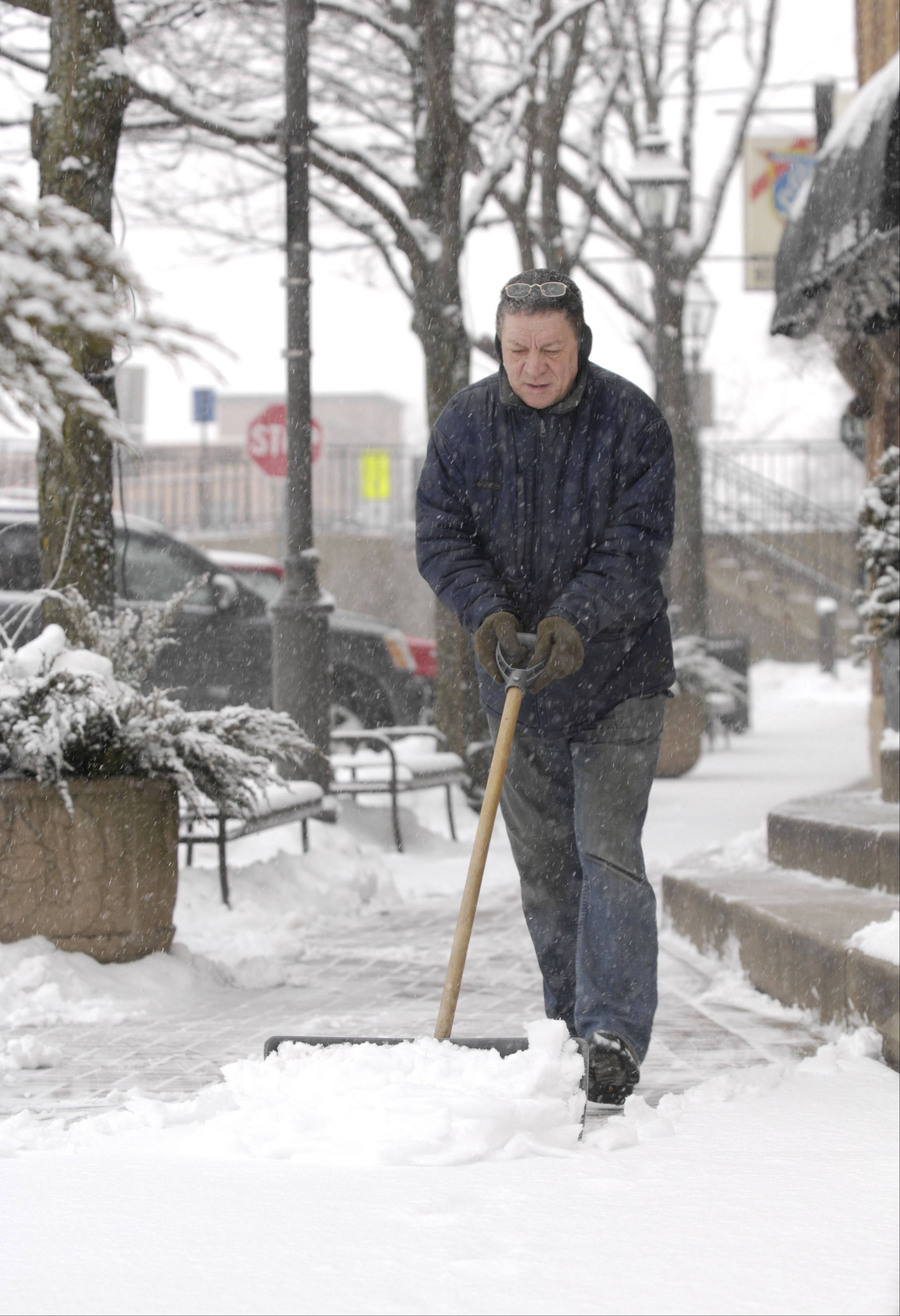 Jim Basile clears the snow off the sidewalk in downtown Lombard Tuesday.