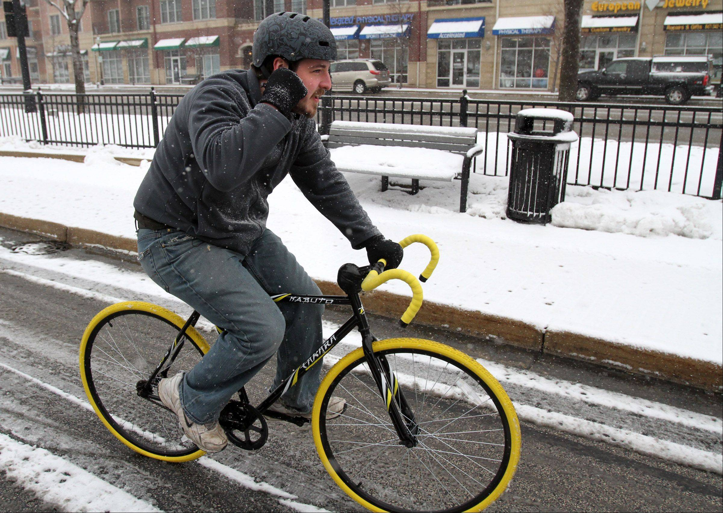 Andy Harwood, of Mount Prospect, is able to talk on his cellphone and maneuver his bike in light snow near the Mount Prospect Metra station Tuesday morning.